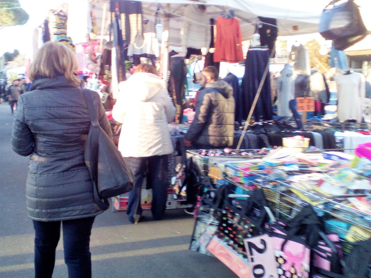retail, rear view, store, incidental people, consumerism, market, choice, for sale, market stall, customer, real people, walking, women, city, casual clothing, outdoors, day, lifestyles, warm clothing, people