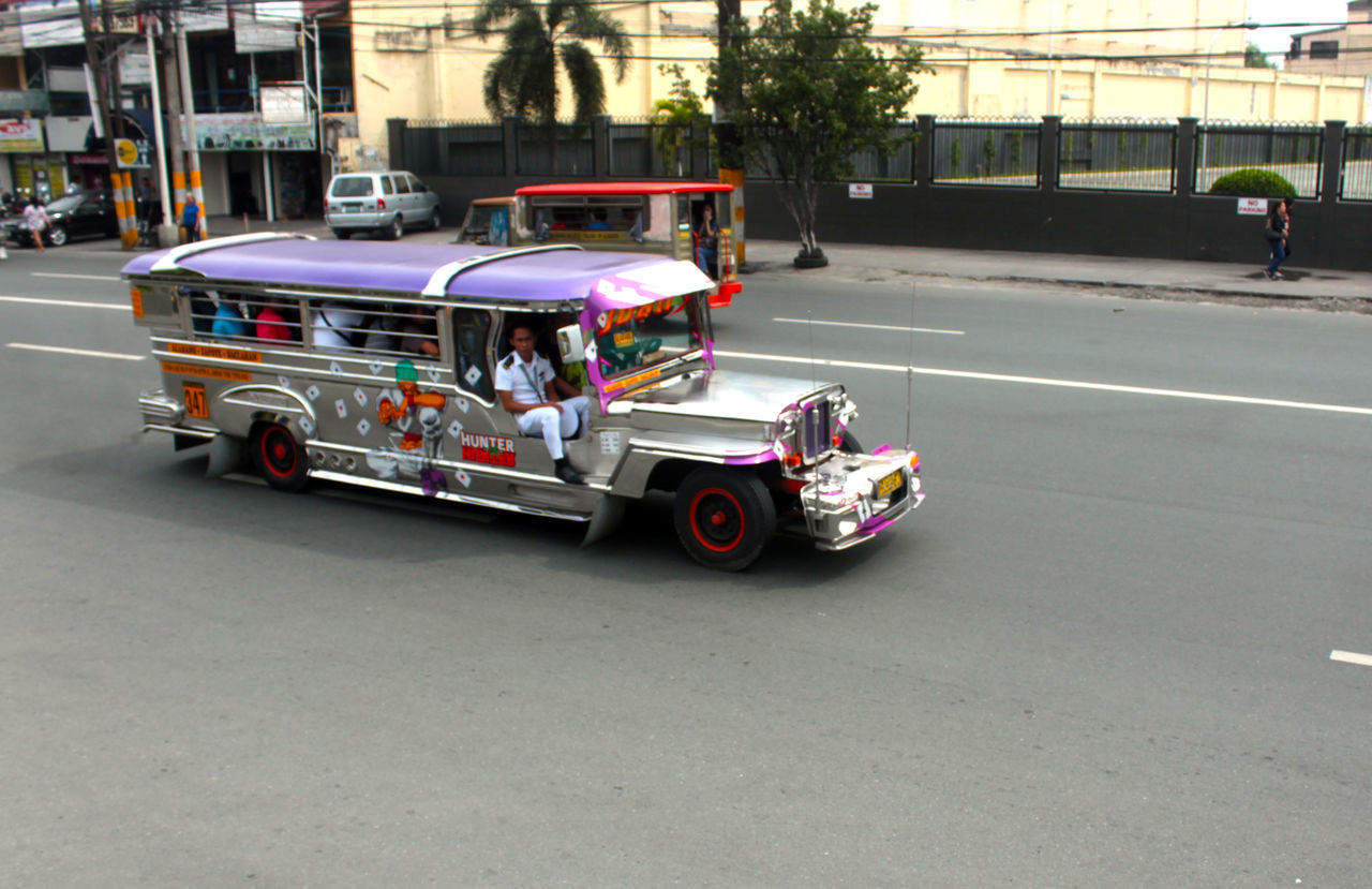 A locally manufactured public utility jeepney plying on the street transporting passengers. Architecture Built Structure City City Life City Street Day Jeep Jeep Life Jeepney Land Vehicle Line Marking Mode Of Transport Multi Colored Outdoors Parked Parking Parking Lot Passenger Seat Passengers Road Stationary Streets Transportation