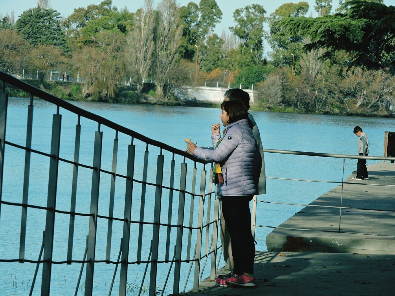 railing, full length, water, real people, river, one person, leisure activity, side view, tree, day, casual clothing, standing, lifestyles, outdoors, nature, women, sky, young adult, people