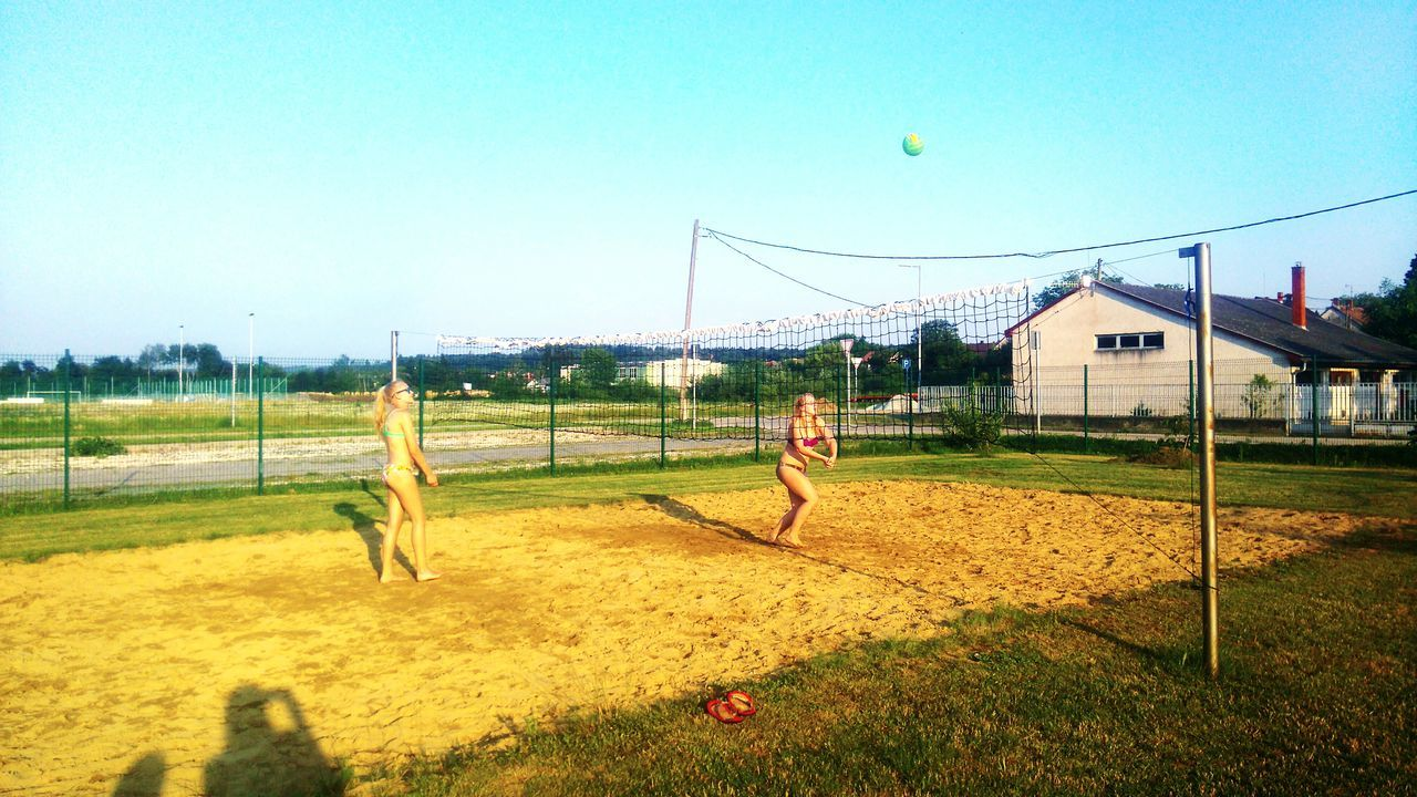 playing, sport, real people, grass, leisure activity, playing field, day, clear sky, lifestyles, soccer, men, outdoors, sky, tree, friendship, nature, beach volleyball, people