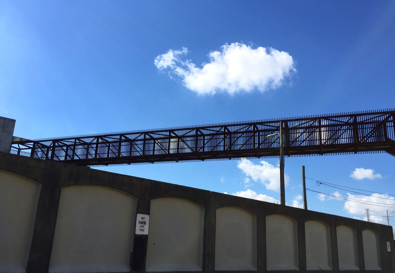 Low Angle View Of Elevated Walkway Over Retaining Wall Against Sky