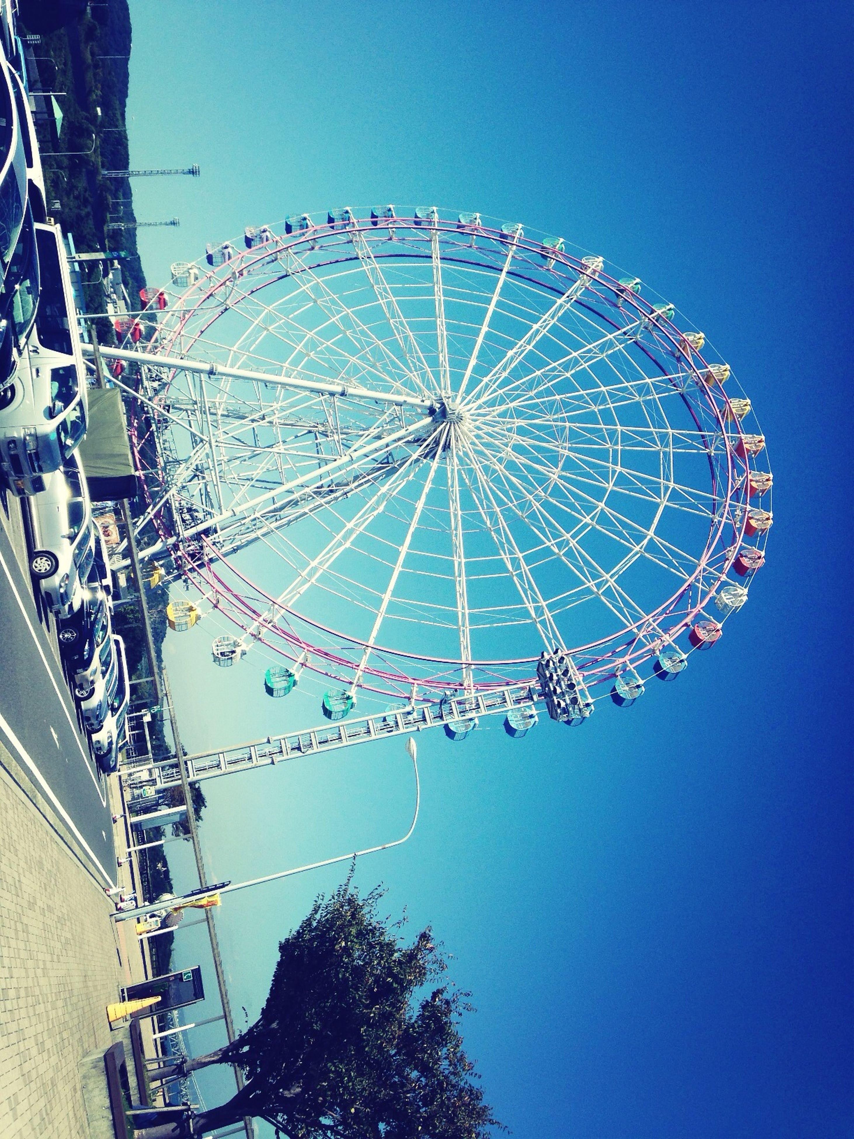 ferris wheel, amusement park, amusement park ride, arts culture and entertainment, low angle view, clear sky, blue, built structure, architecture, sky, fun, building exterior, copy space, outdoors, enjoyment, circle, big wheel, incidental people, large, day