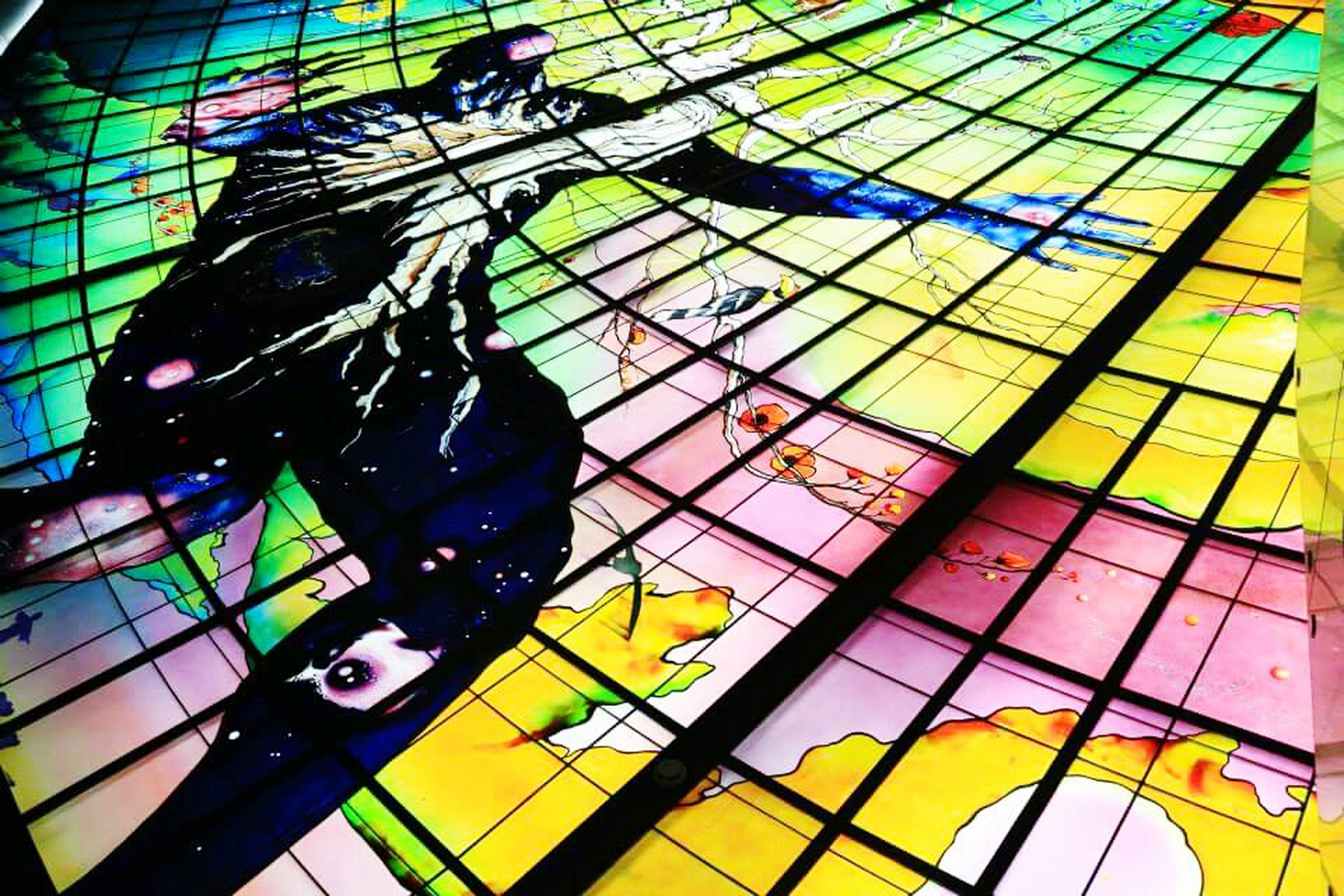 yellow, multi colored, art and craft, art, creativity, low angle view, built structure, architecture, pattern, graffiti, indoors, design, human representation, day, glass - material, animal representation, blue, no people, window