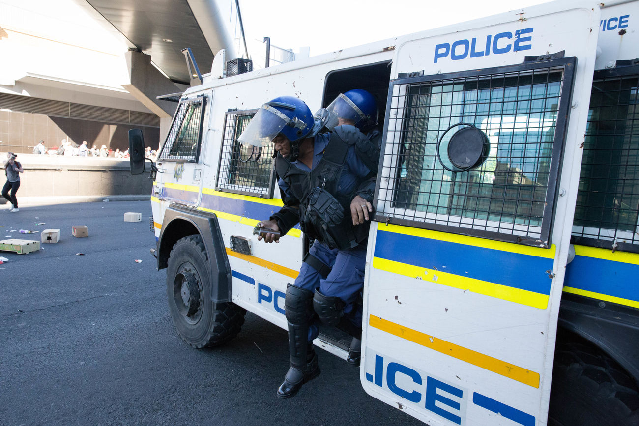 A South African Policeman with stun grenade in hand disembarks from a RG-12 Nyala to disperse student protestors from the Fees Must Fall movement. Cape Town Expertise Feesmustfall Full Length Helmet Land Vehicle Mode Of Transport Police Force South Africa Transportation The Photojournalist - 2017 EyeEm Awards