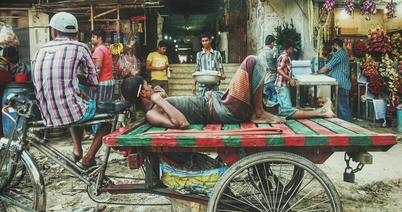 lifestyles, leisure activity, sitting, bicycle, men, person, casual clothing, mode of transport, chair, land vehicle, built structure, relaxation, transportation, architecture, full length, day, side view, arts culture and entertainment