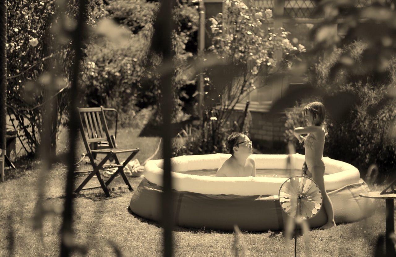Boy In Wading Pool Looking At Sister In Yard