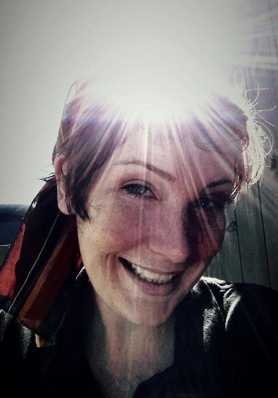 Portrait Of Smiling Woman Against Bright Sun