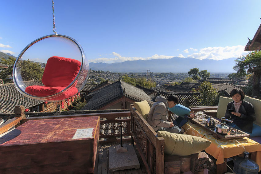 Lijiang, China - November 10, 2016: People relaxing on a couch and enjoying the view of Lijiang Old Town on a sunny day Adult ASIA China Dali Yunnan Day Hotel Lijiang Outdoors People Roof Top Shangri-La Yunnan