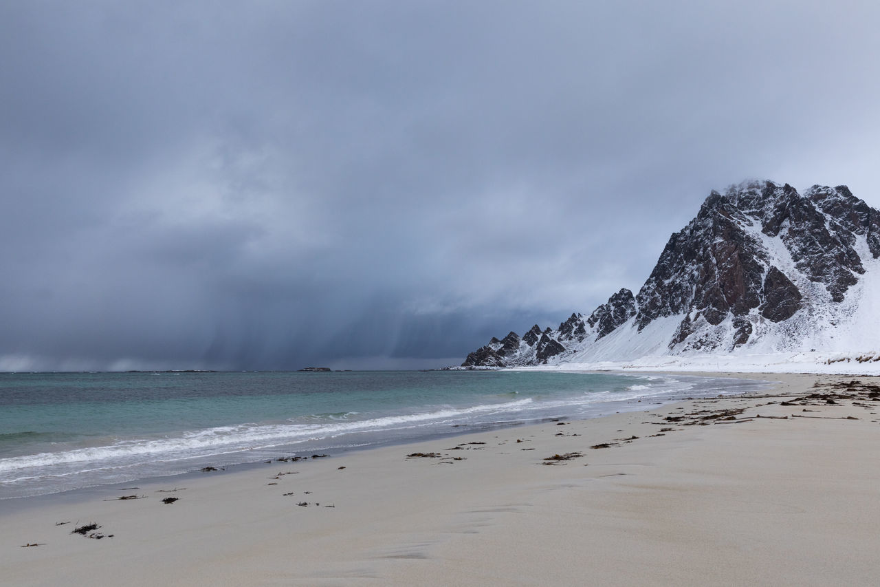 Snowcapped mountain at beach and dark rainclouds over sea coming closer Beach Beauty In Nature Cloud - Sky Cloudscape Cold Temperature Dark Dramatic Sky Extreme Weather Gray Horizon Over Water Lofoten And Vesteral Islands Moody Sky Mountain Norwegian Sea Power In Nature Rain Sand Scenics Sea Sky Storm Storm Cloud Wave Weather Winter The Great Outdoors - 2017 EyeEm Awards