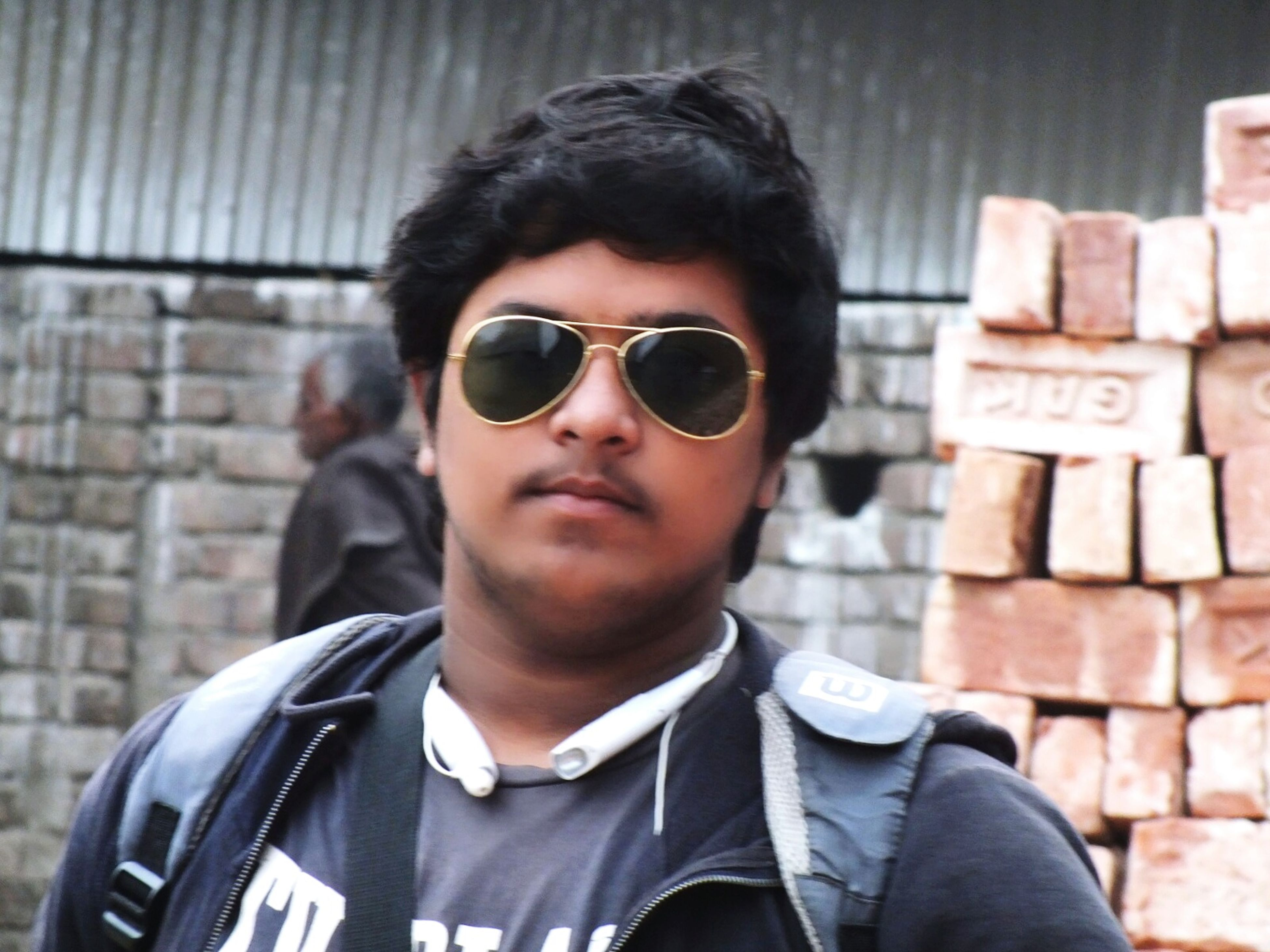 portrait, looking at camera, front view, lifestyles, young adult, person, sunglasses, headshot, casual clothing, young men, focus on foreground, leisure activity, close-up, smiling, head and shoulders, handsome, waist up, standing