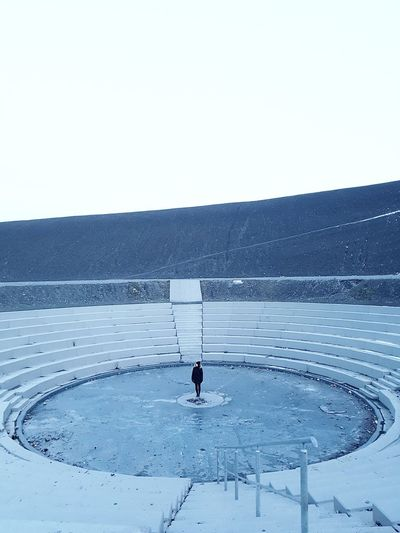 Iceland? One Person Winter Cold Temperature Frozen Water Female Model Lonliness Hill Amphitheater Abandoned Weathered Full Frame Adapted To The City Clear Sky Round Architecture Stairs Symmetry Minimalism Shades Of Grey Shades Of Blue Ice Real People The Architect - 2017 EyeEm Awards The Great Outdoors - 2017 EyeEm Awards