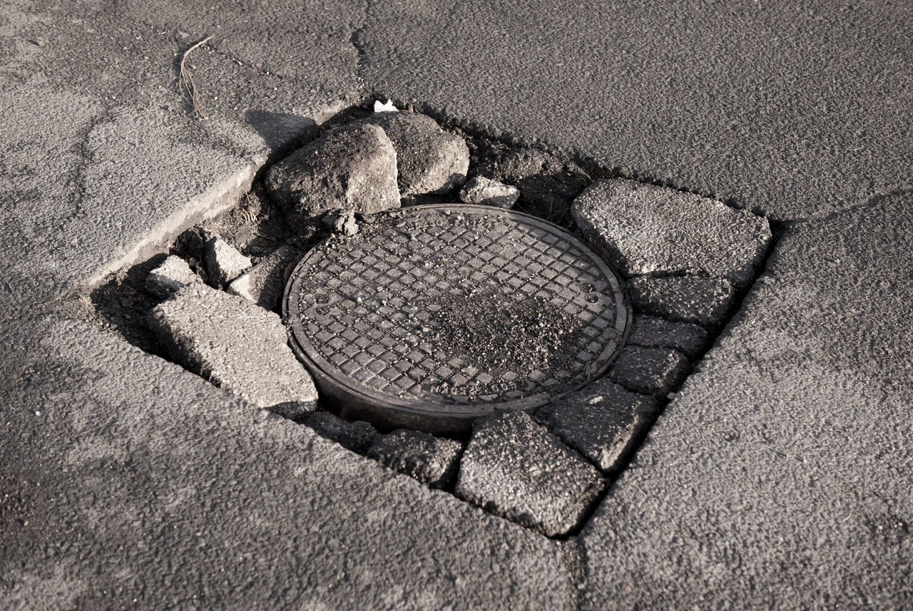 Large pothole in asphalt and circular manhole cover of sewage well in road, close metal sewer cover in Warsaw, Poland, horizontal orientation, nobody. Asphalt Broken Chuckhole Chuckholes Cover Cracked Crushed Damaged Dilapidated Drain Drainage Hole Manhole  No People Plug Pothole Potholes Road Sewer Sewer Cover Street Way