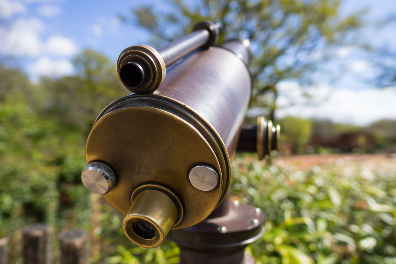 Old-style telescope with big blurred tree in the background Close-up Coin-operated Binoculars Day Focus On Foreground Gold Colored No People Outdoors Sky Sunlight Telescope Tree