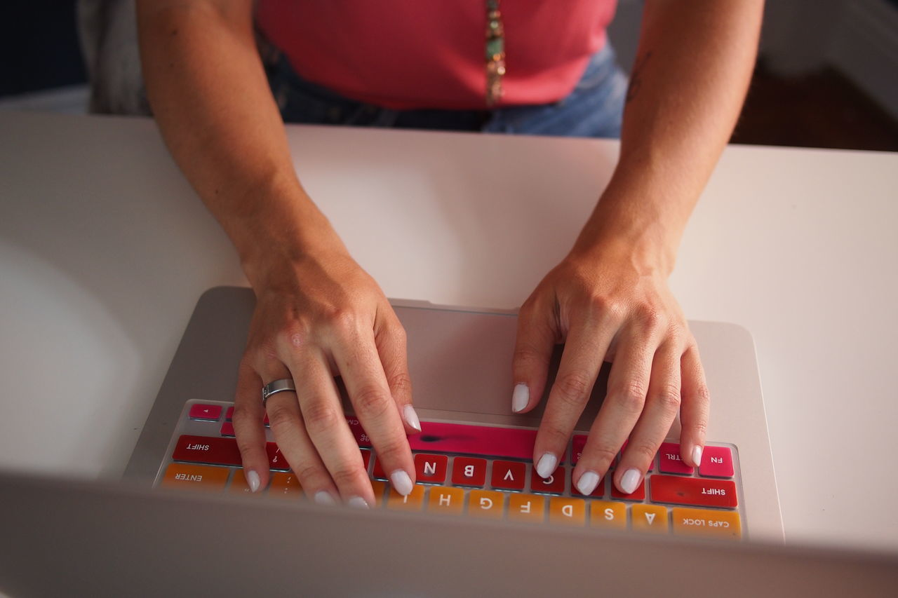 Cropped Image Of Woman Hand Using Laptop On Table