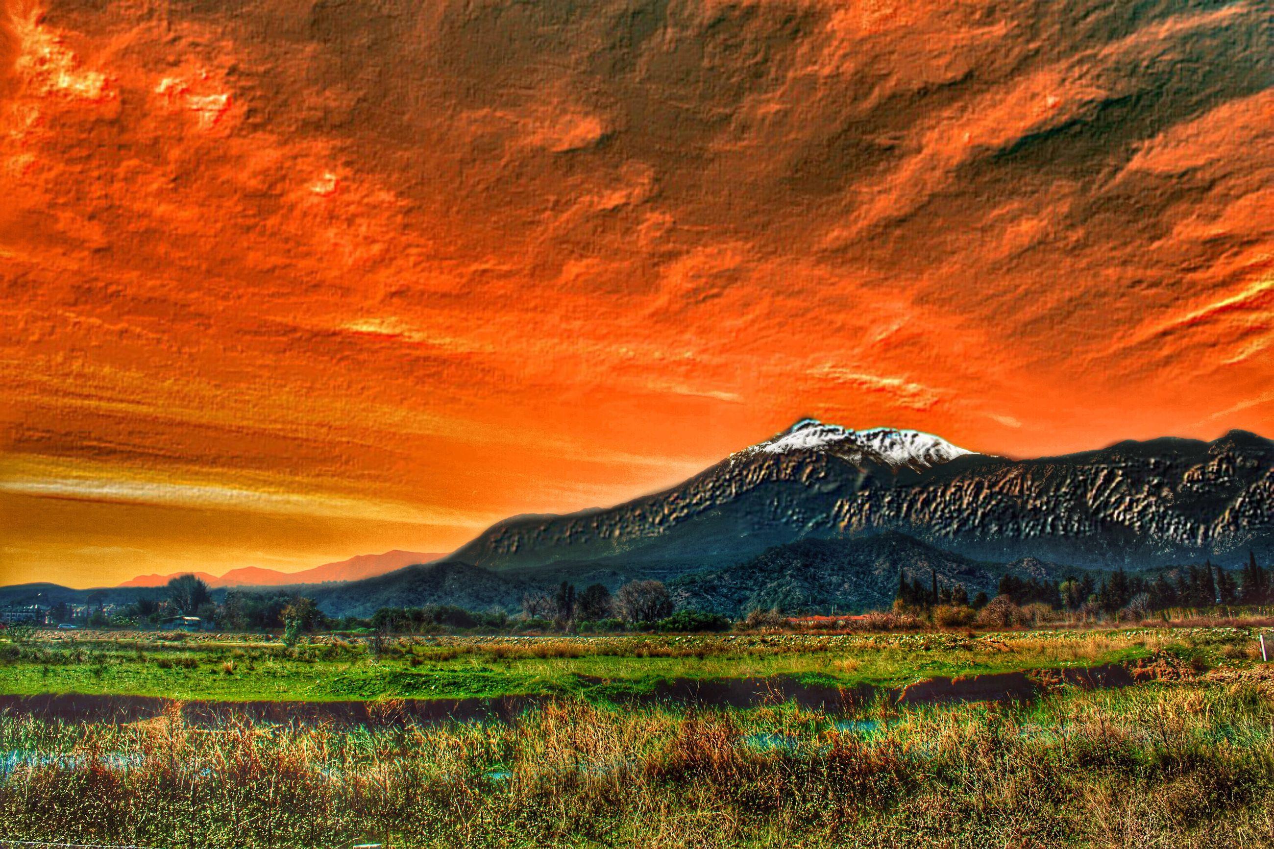 tranquil scene, scenics, sunset, tranquility, beauty in nature, landscape, orange color, mountain, sky, grass, nature, idyllic, field, cloud - sky, non-urban scene, mountain range, dramatic sky, plant, remote, cloud