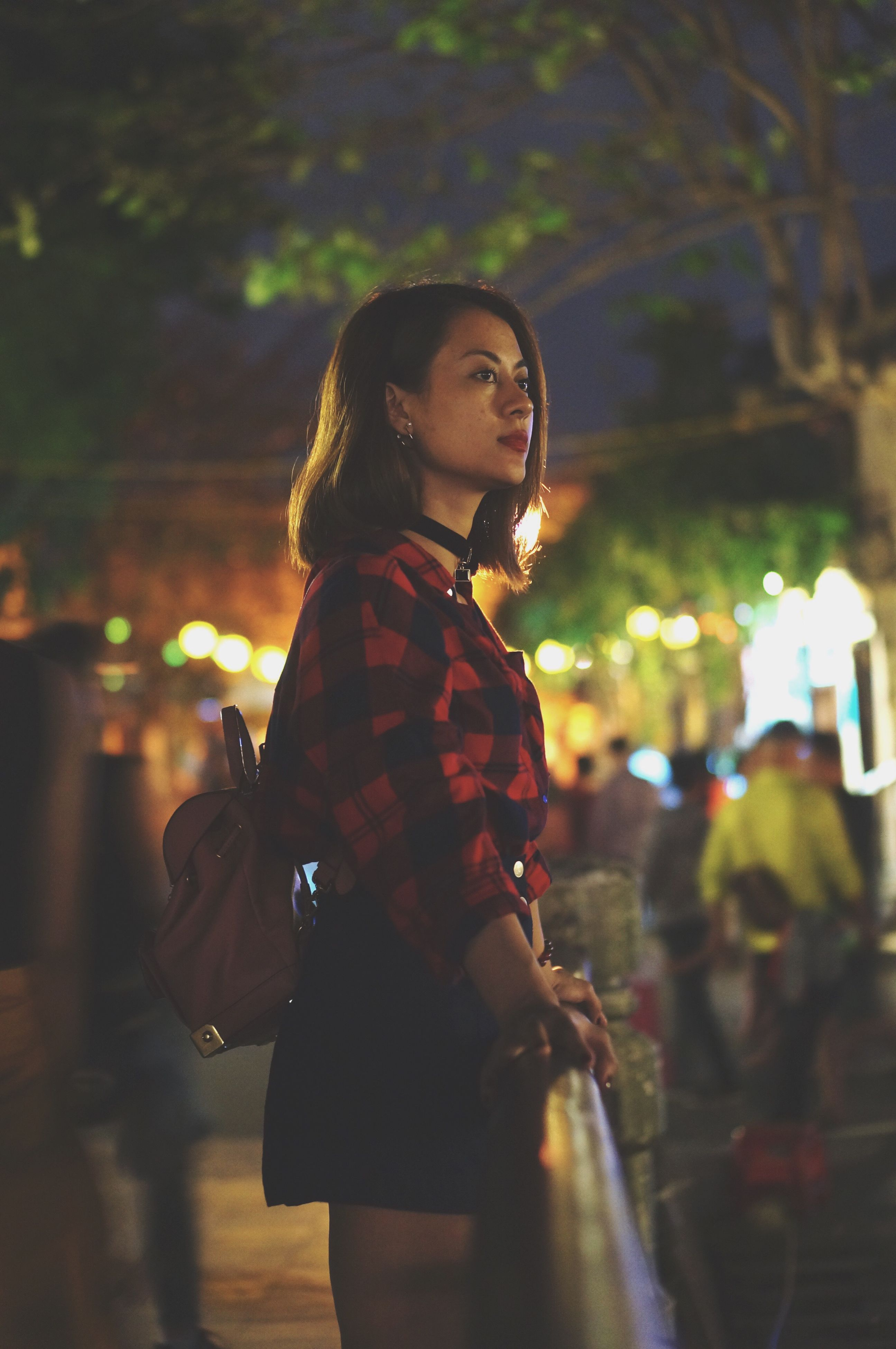 night, three quarter length, shopping bag, real people, focus on foreground, street, lifestyles, leisure activity, one person, outdoors, young adult, standing, young women, women, illuminated, city, people