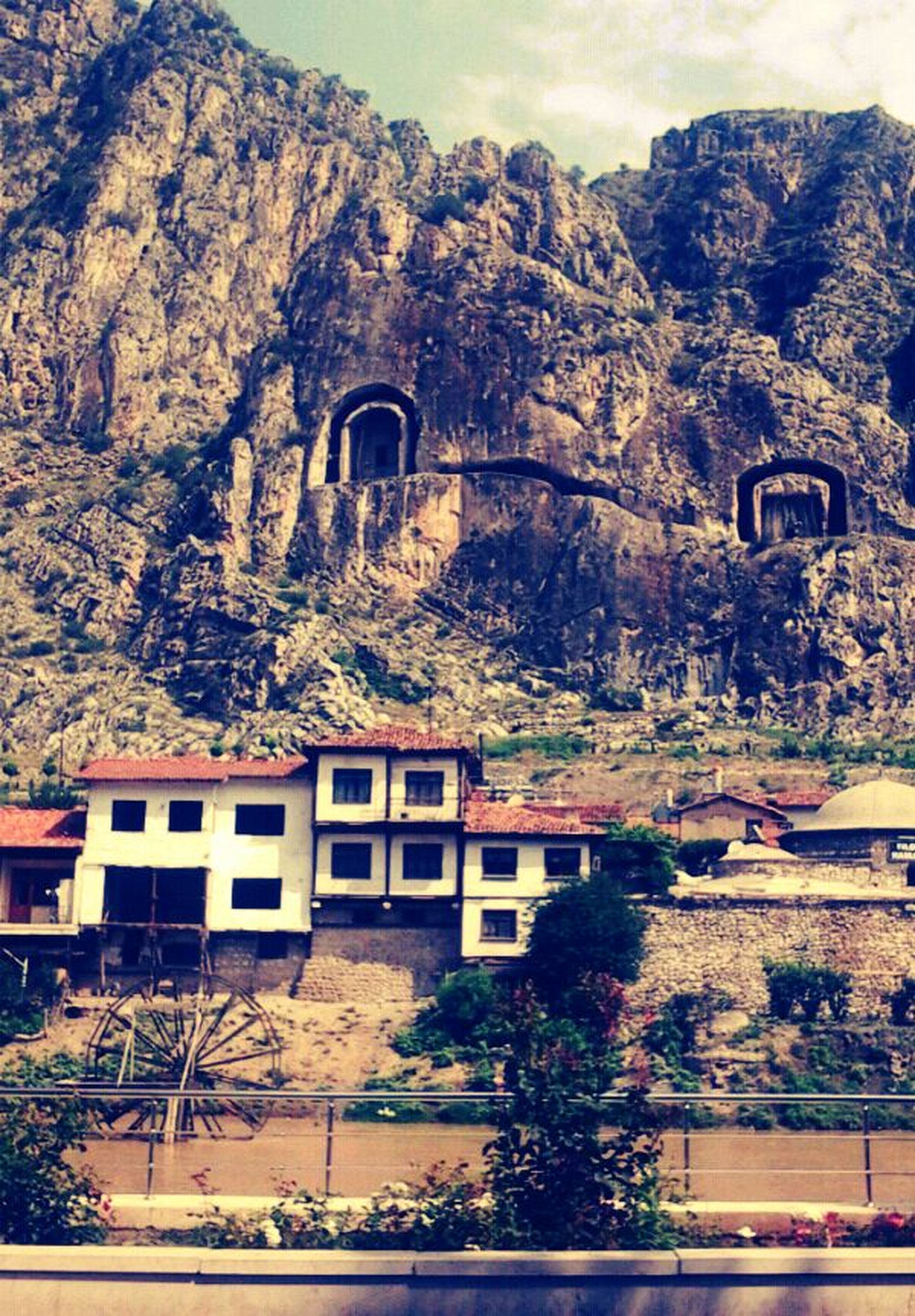 architecture, built structure, building exterior, tree, mountain, sky, arch, house, day, outdoors, nature, residential structure, no people, history, travel destinations, residential building, old, town, travel, growth