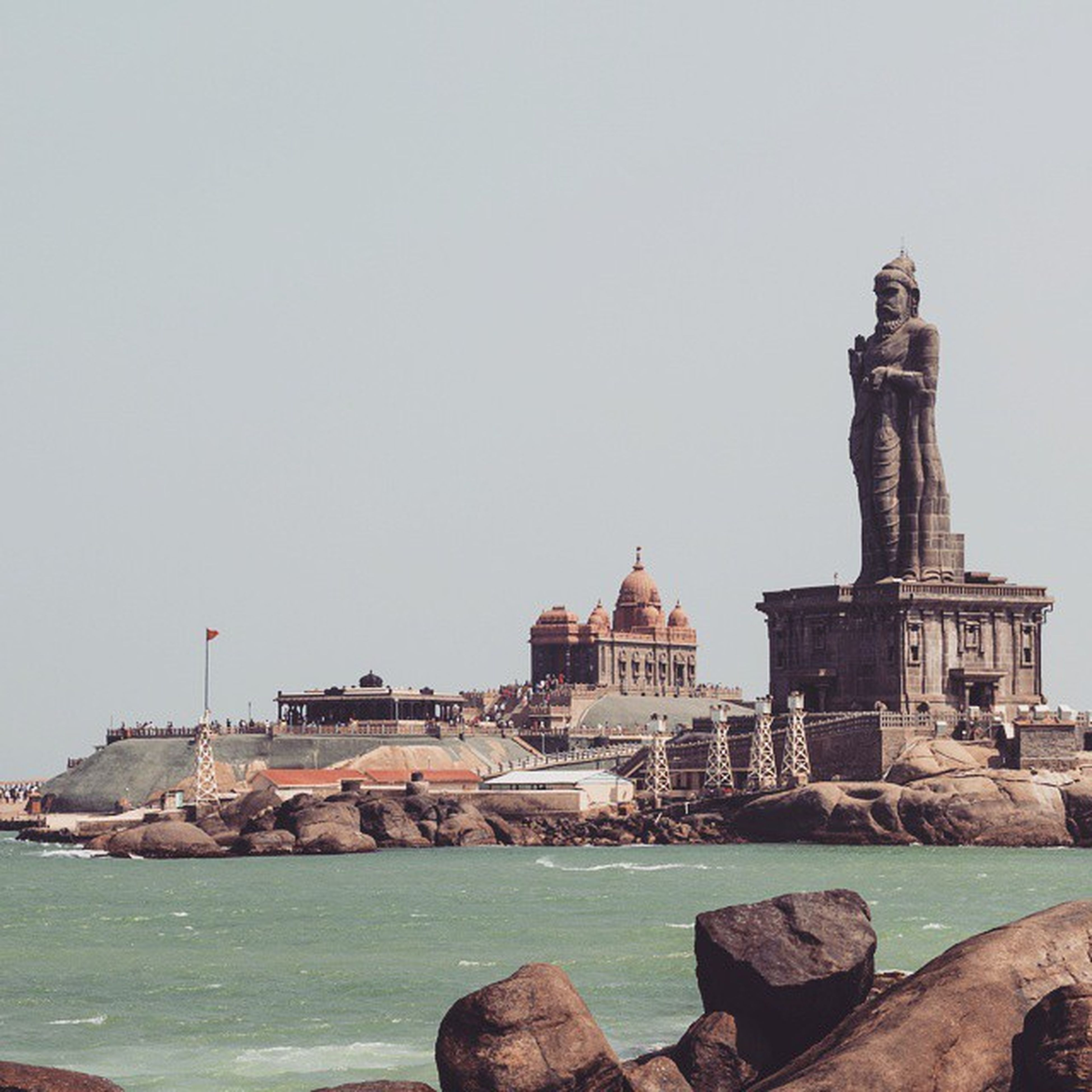clear sky, water, architecture, copy space, built structure, building exterior, sea, rock - object, famous place, travel destinations, history, travel, day, tourism, statue, international landmark, waterfront, sculpture, outdoors, lighthouse