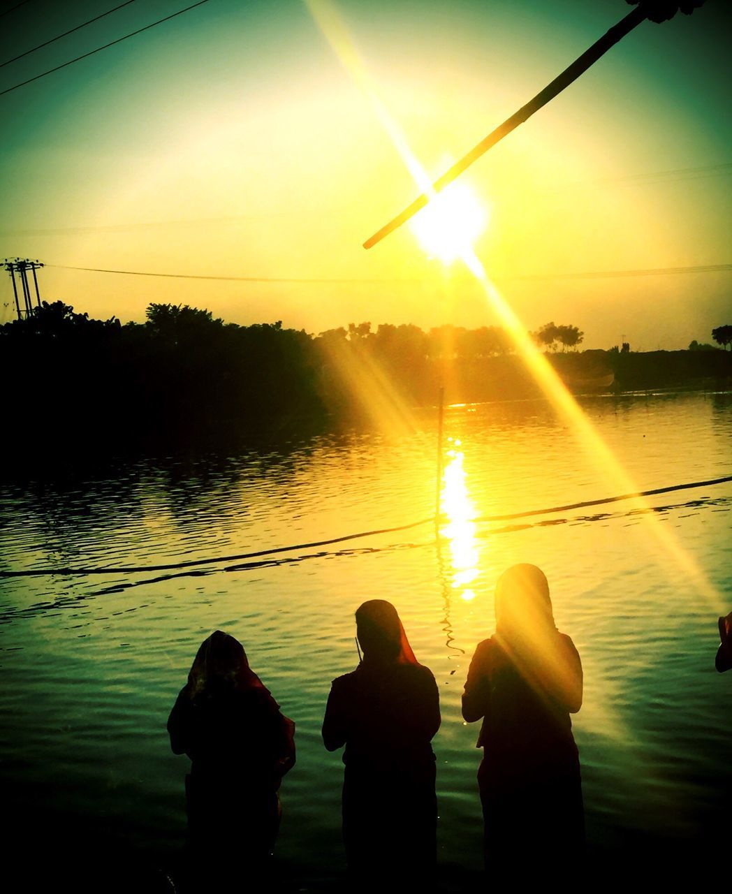 sunset, water, silhouette, sun, nature, sunbeam, sunlight, beauty in nature, real people, scenics, lake, reflection, men, standing, outdoors, tranquility, tranquil scene, leisure activity, sky, fishing pole, two people, lifestyles, togetherness, day, people