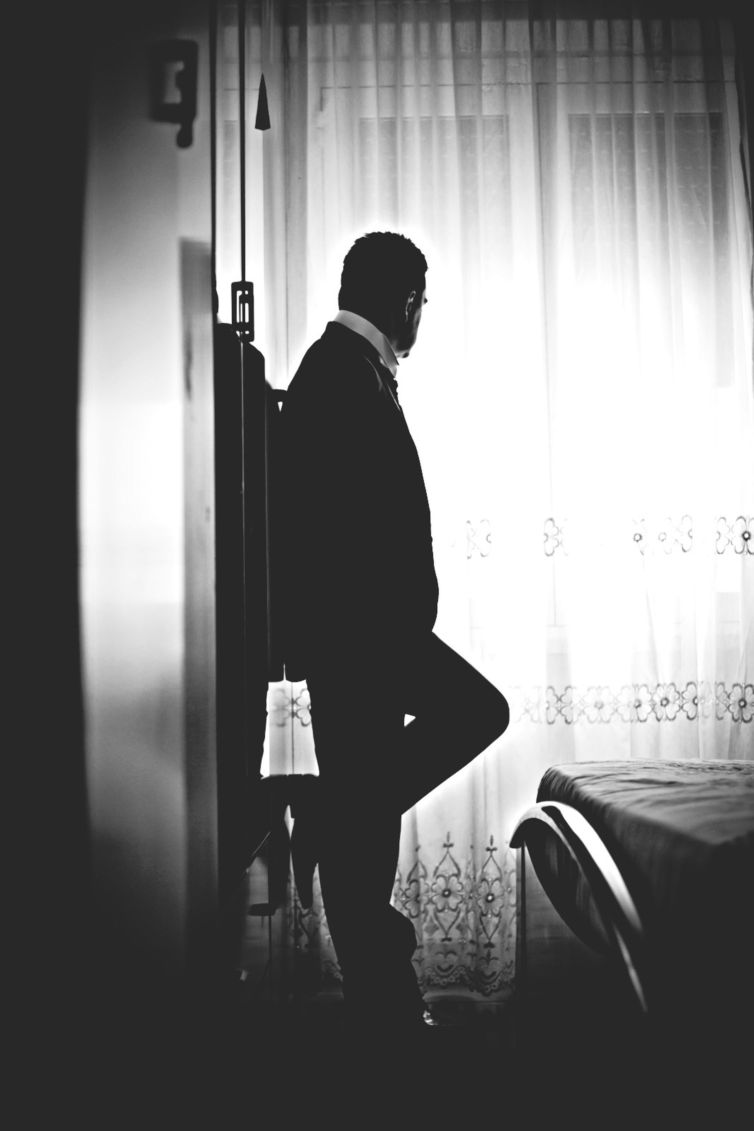 indoors, lifestyles, rear view, men, home interior, leisure activity, table, sitting, window, full length, standing, casual clothing, person, domestic life, chair, domestic room, curtain, silhouette