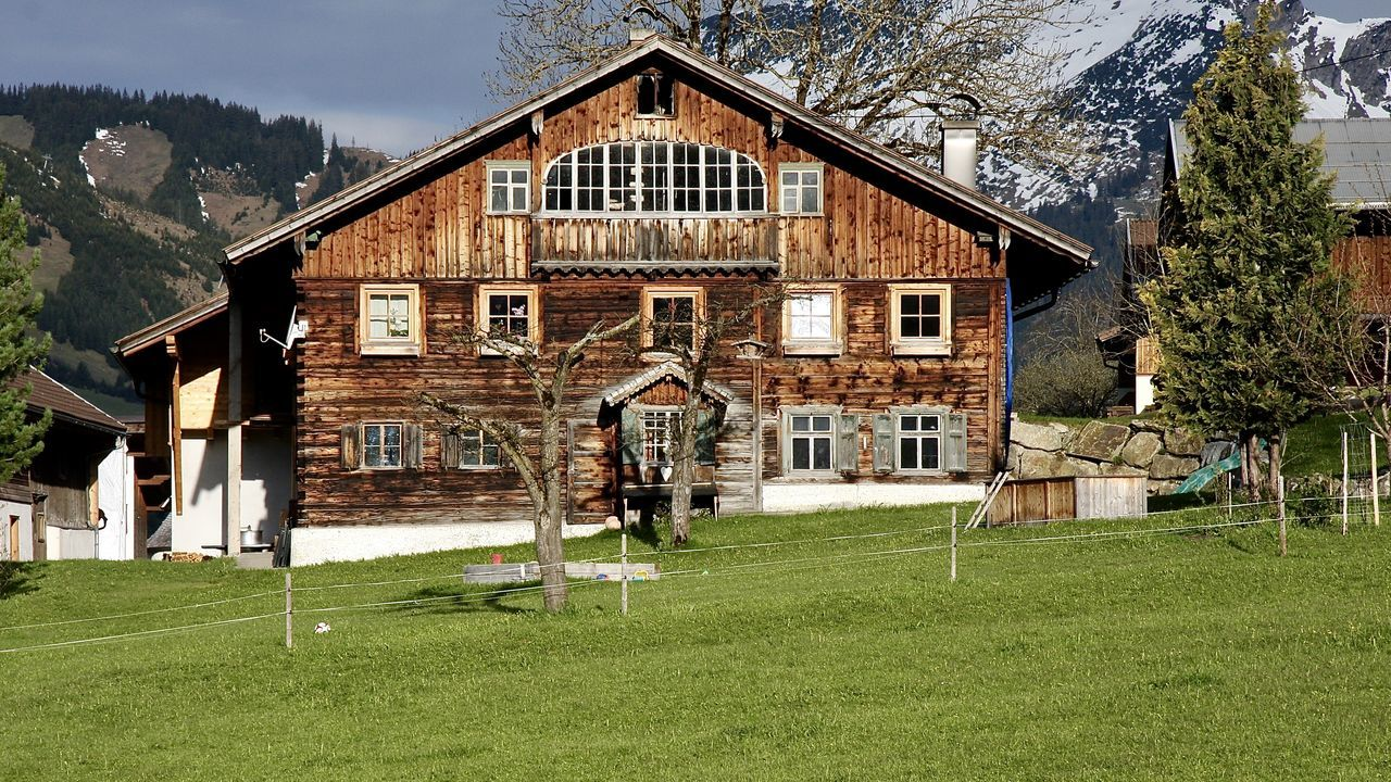scenic view of traditional house in tannheimer tal, tirol Architecture Beauty In Nature Building Exterior Grass Greenery Holiday House Landscape Life Light Mountain Nature Outdoors Scenics Sky Snowcapped Mountain Spring Tannheimer Tal Tirol  Traditional Travel Tree Wooden