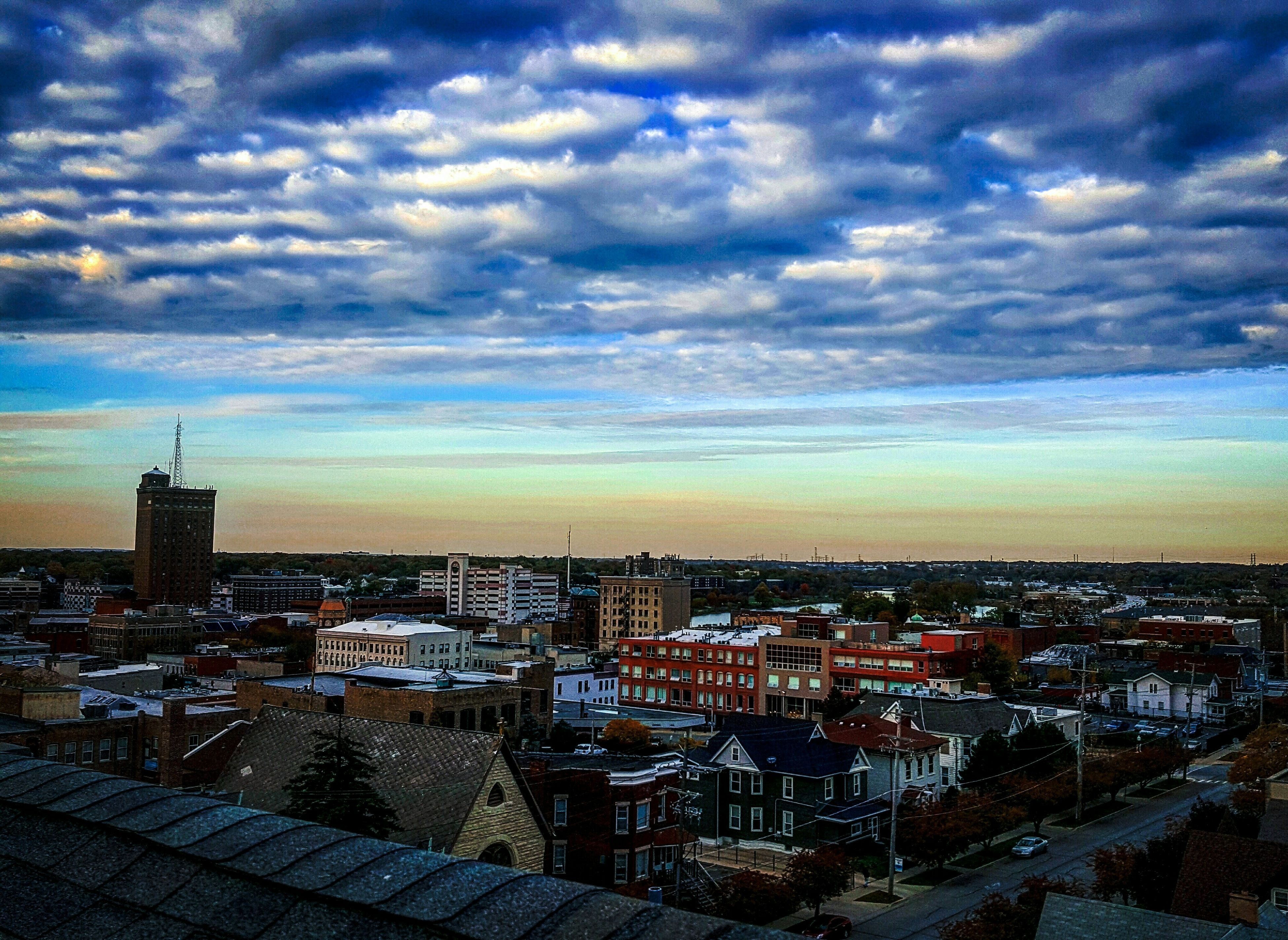 building exterior, architecture, sky, built structure, cityscape, city, cloud - sky, cloudy, sunset, high angle view, residential district, cloud, residential building, water, crowded, tower, city life, residential structure, weather, dusk