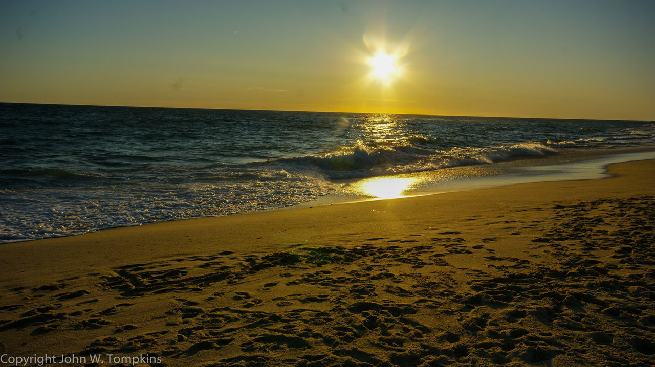 sea, sunset, beach, beauty in nature, sand, scenics, sun, nature, horizon over water, water, yellow, tranquil scene, sunlight, tranquility, sky, outdoors, no people, wave, day