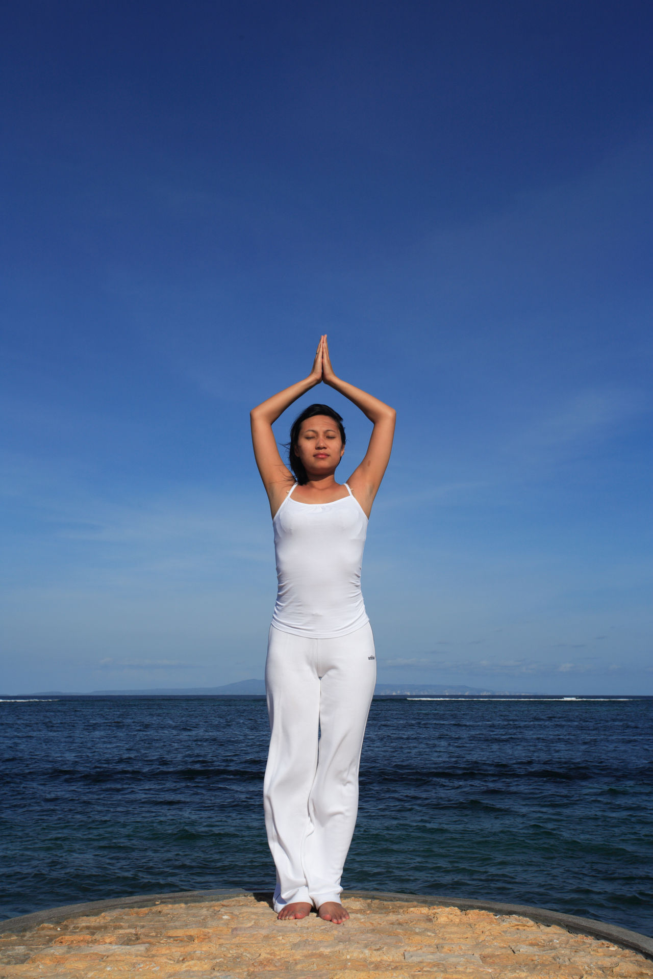 Arms Raised Beach Blue Clear Sky Exercising Full Length Hands Clasped Healthy Lifestyle Human Arm Human Body Part Limb Meditating One Person Outdoors People Relaxation Exercise Religion Sea Sky Spirituality Stretching Summer Vacations Yoga Zen-like