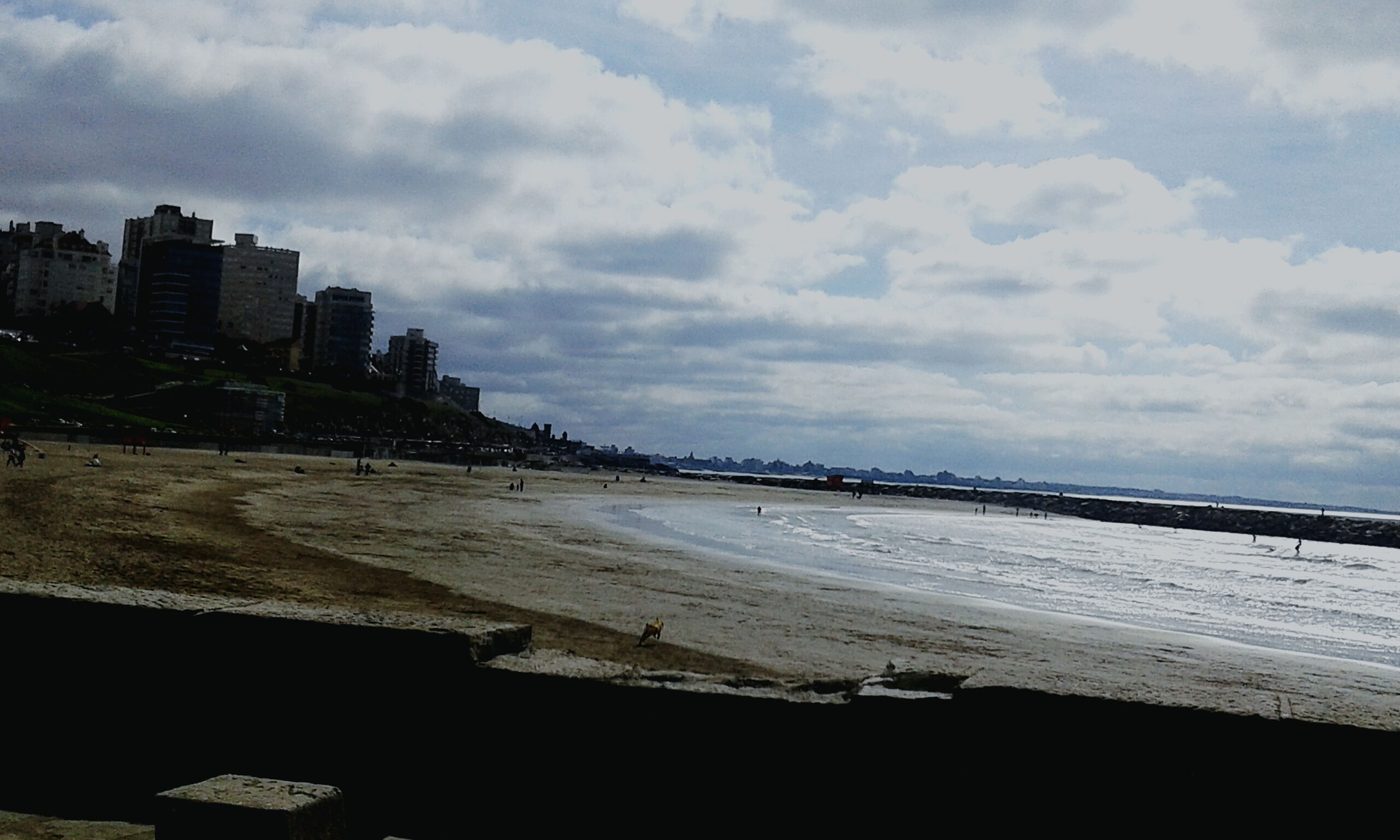 sky, building exterior, architecture, built structure, water, cloud - sky, sea, beach, cloudy, city, cloud, shore, incidental people, nature, day, outdoors, sand, high angle view, cityscape, bird