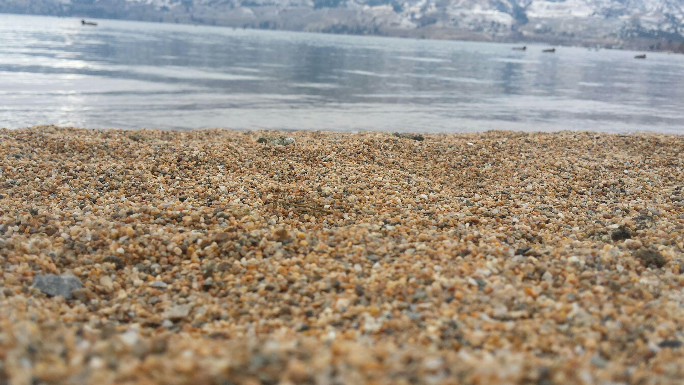 beach, water, shore, sand, tranquility, surface level, sea, tranquil scene, nature, scenics, beauty in nature, pebble, sky, day, idyllic, selective focus, outdoors, coastline, no people, remote