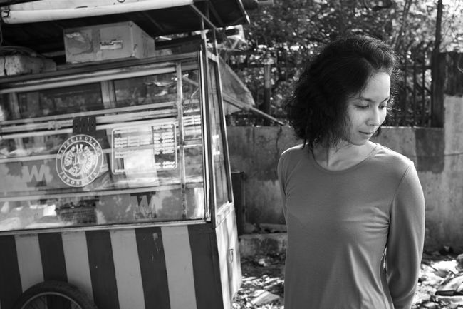 on the hot streets of surabaya -- july 2016 Asian Girl B&w Street Photography Back Street Beautiful Woman Black And White Photography Bokeh Daytime Focus On Foreground Fujifilm_xseries Java Indonesia Kaki Lima Lifestyle Photo Shoot Long Black Hair Looking Away Monochrome Natural Beauty Outdoors Portrait Of A Woman Street Scene Street Vendor Surabaya Waist Up Fine Art Photography