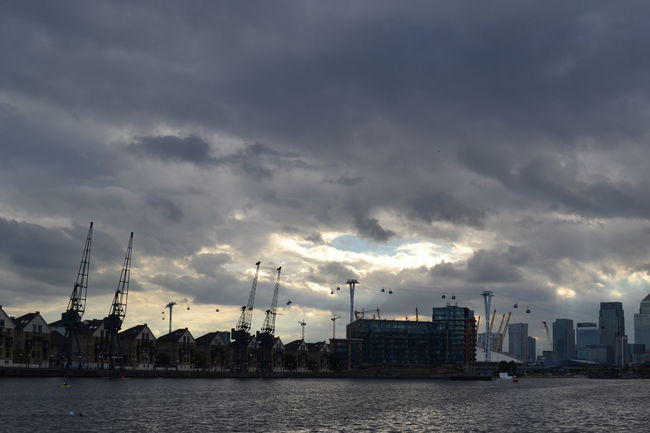Gloomy Day Riverbank Moody Sky Hole Of Light Cloudy Day In Front Of Dramatic Sky Builings In The Distance Waterfront