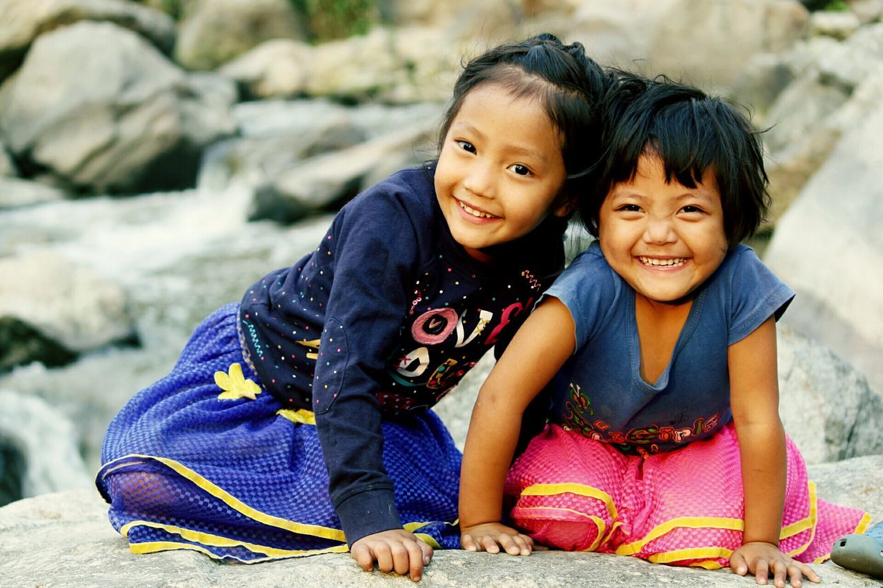 two people, looking at camera, childhood, real people, smiling, happiness, sitting, togetherness, portrait, full length, elementary age, girls, leisure activity, outdoors, day, bonding, boys, nature, people