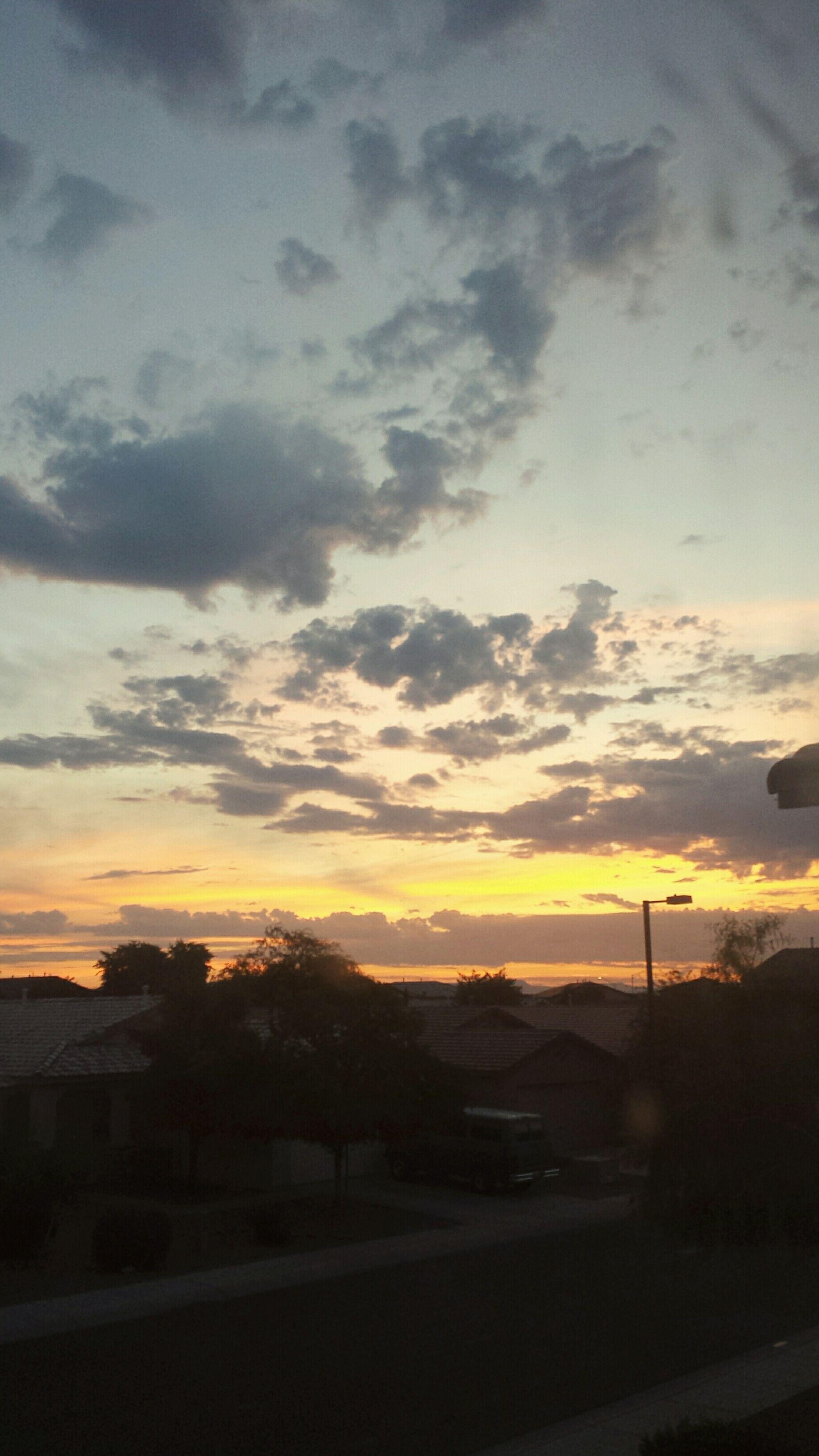 sunset, sky, cloud - sky, road, transportation, silhouette, landscape, scenics, orange color, beauty in nature, car, cloudy, nature, cloud, street, dramatic sky, tranquil scene, building exterior, built structure, mountain