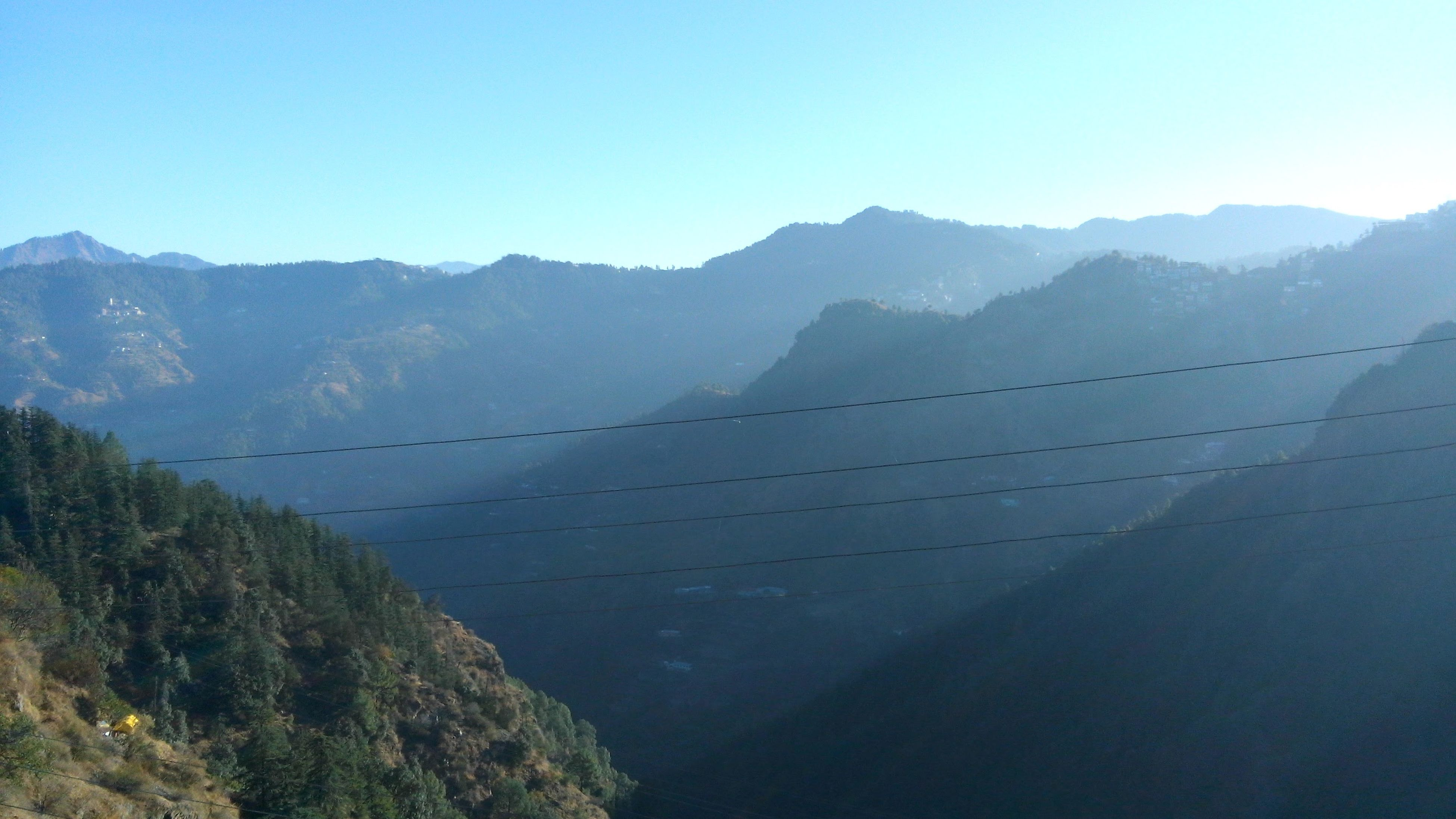 mountain, cable, scenics, clear sky, power line, mountain range, tree, landscape, tranquil scene, non-urban scene, nature, tranquility, beauty in nature, remote, blue, physical geography, day, geology, outdoors, steel cable, majestic, no people, countryside, solitude, power supply