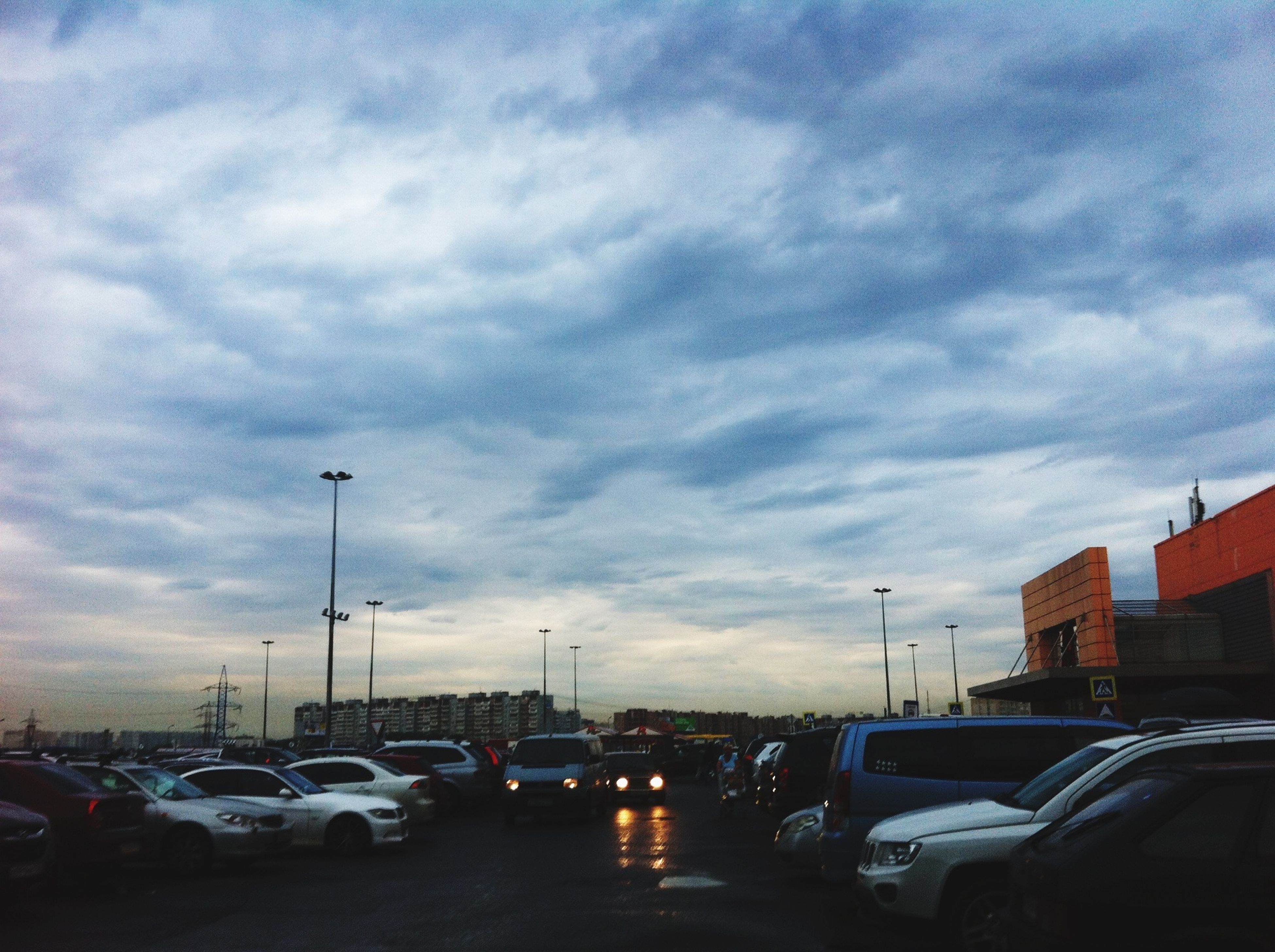 transportation, car, land vehicle, mode of transport, sky, street, road, cloud - sky, stationary, parking, parking lot, cloudy, building exterior, on the move, traffic, parked, city, street light, architecture, built structure