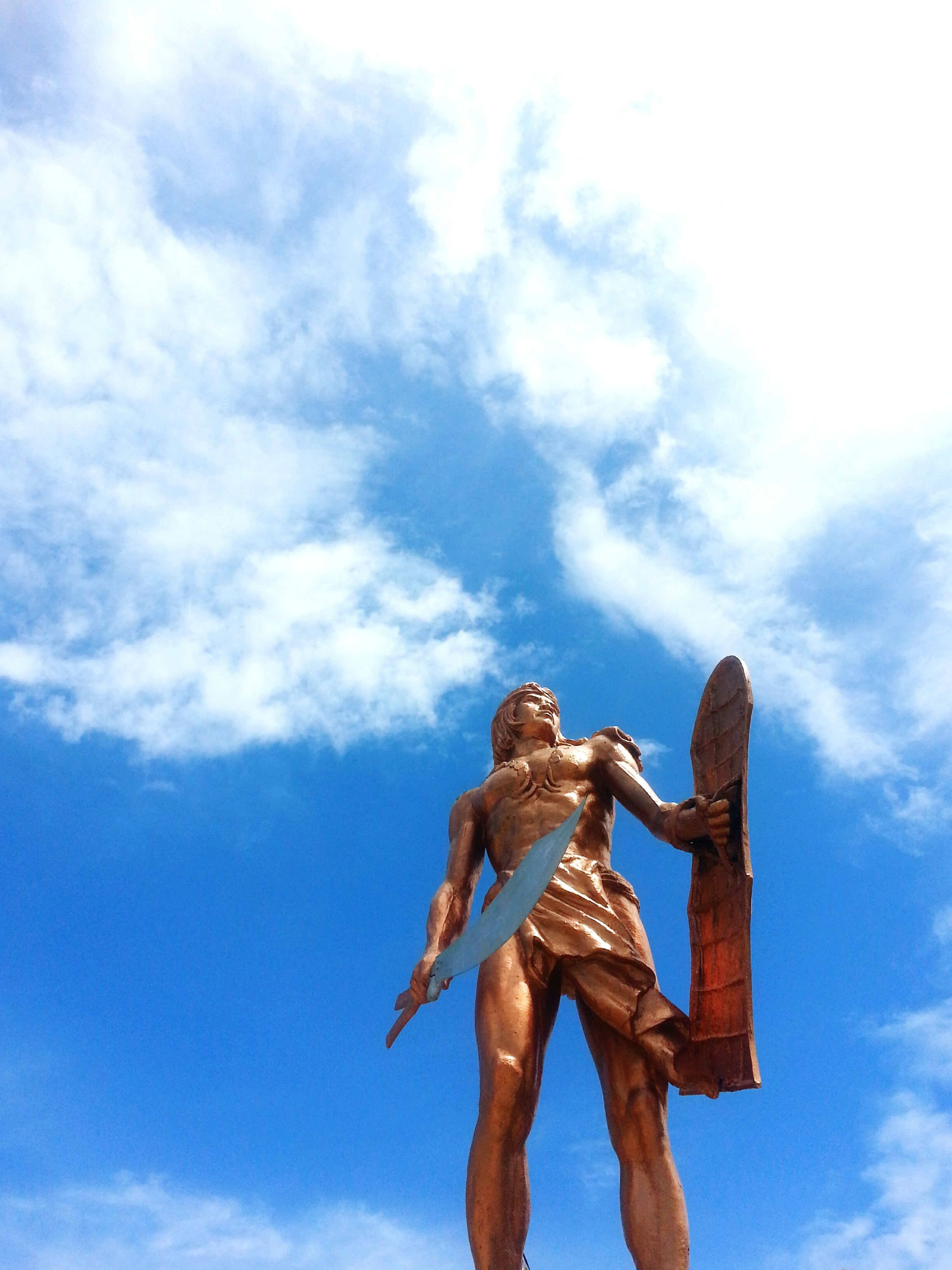 low angle view, sculpture, sky, statue, art and craft, human representation, art, cloud - sky, creativity, cloud, animal representation, cloudy, day, outdoors, craft, no people, carving - craft product, angel