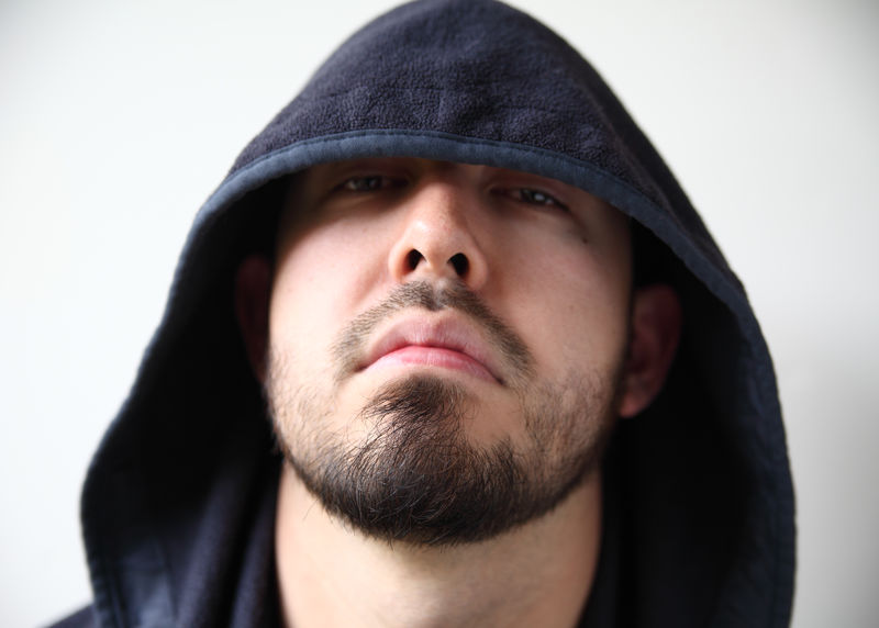Man in hoodie looks hostile Bearded Black Hoodie Close-up Confidence  Cool Attitude Front View Headshot Hostile Human Face Indoors  Mysterious Natural Light One Person Portrait Serious Threatening Tough Guy Urban Young Men