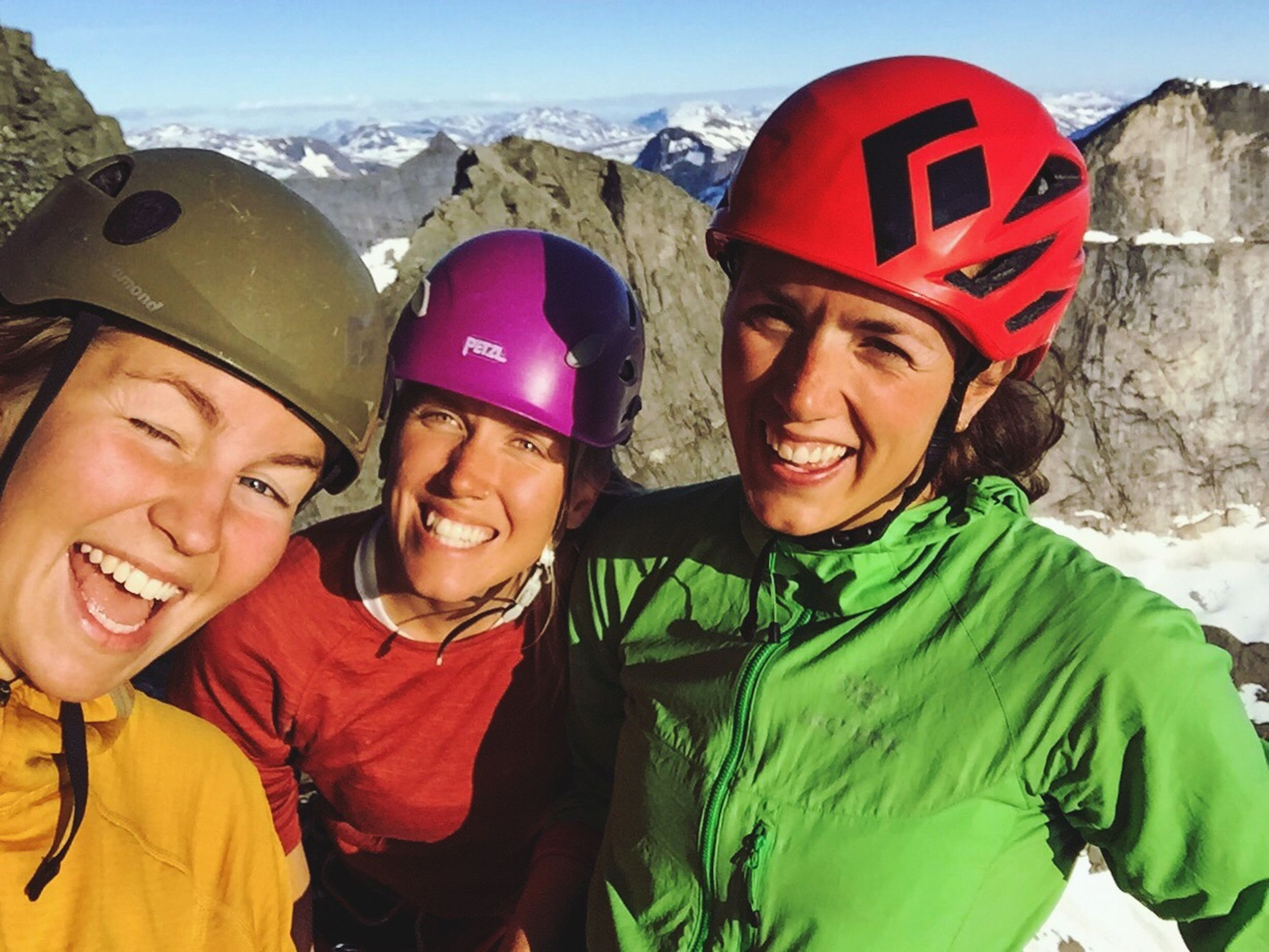 smiling, real people, leisure activity, happiness, togetherness, headwear, mountain, day, friendship, lifestyles, portrait, looking at camera, sports helmet, young women, outdoors, bonding, sport, cheerful, helmet, young adult, sports clothing, close-up, sky