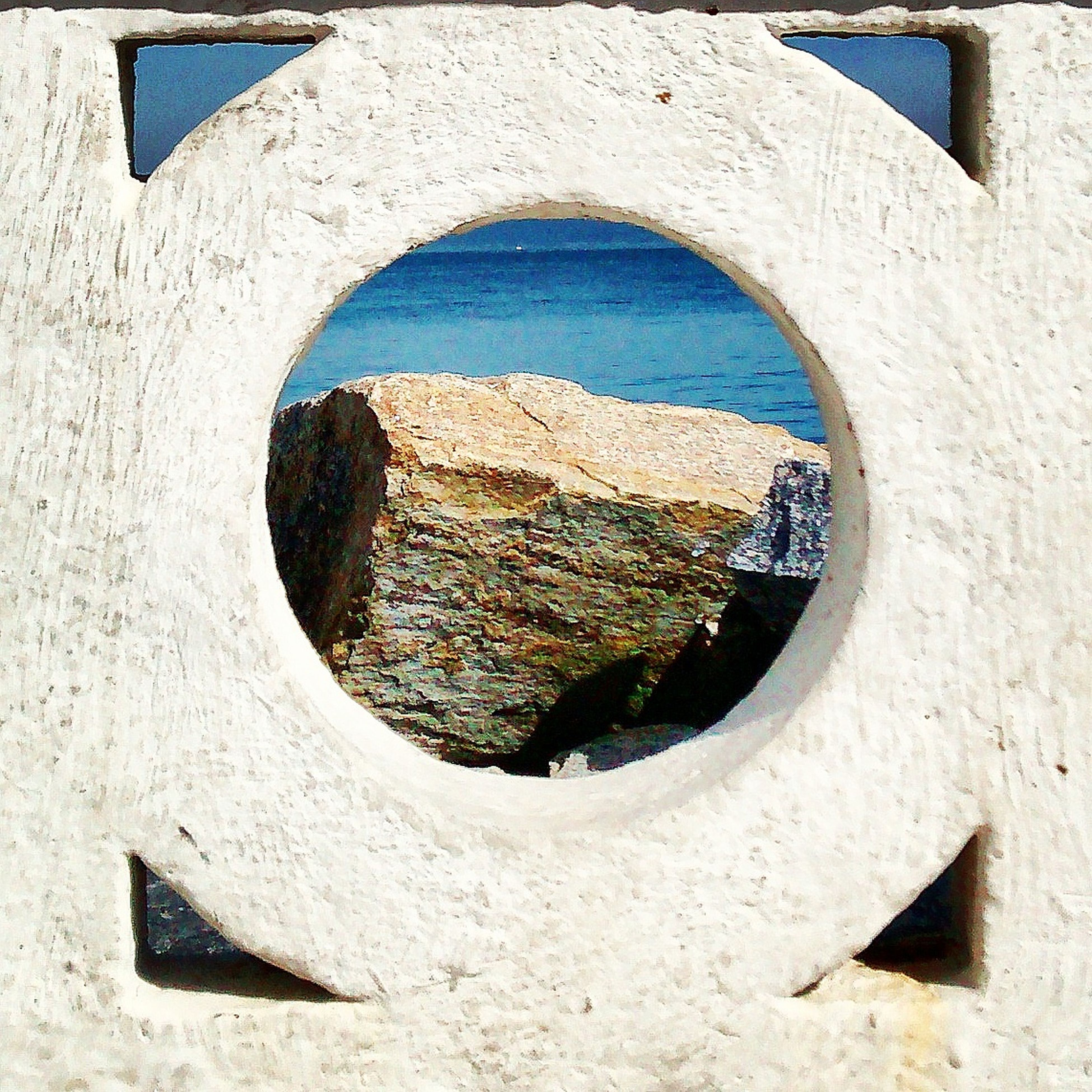 circle, architecture, built structure, geometric shape, building exterior, textured, shape, old, day, wall - building feature, blue, close-up, weathered, hole, no people, outdoors, damaged, wall, pattern, stone wall