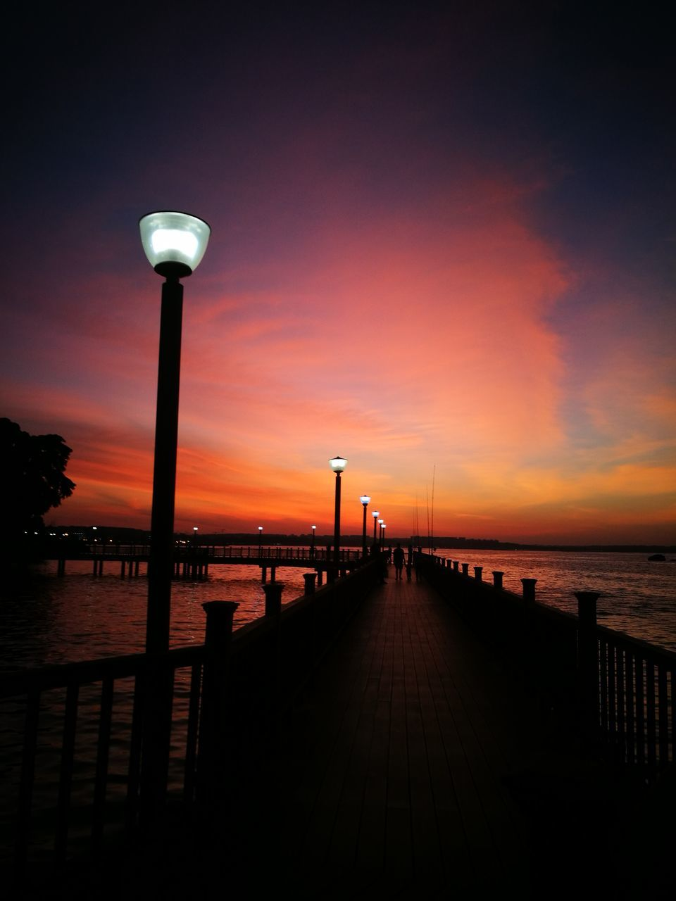 sea, sunset, water, railing, tranquil scene, beauty in nature, horizon over water, pier, nature, scenics, beach, sky, street light, tranquility, silhouette, jetty, outdoors, travel destinations, built structure, no people, architecture, day