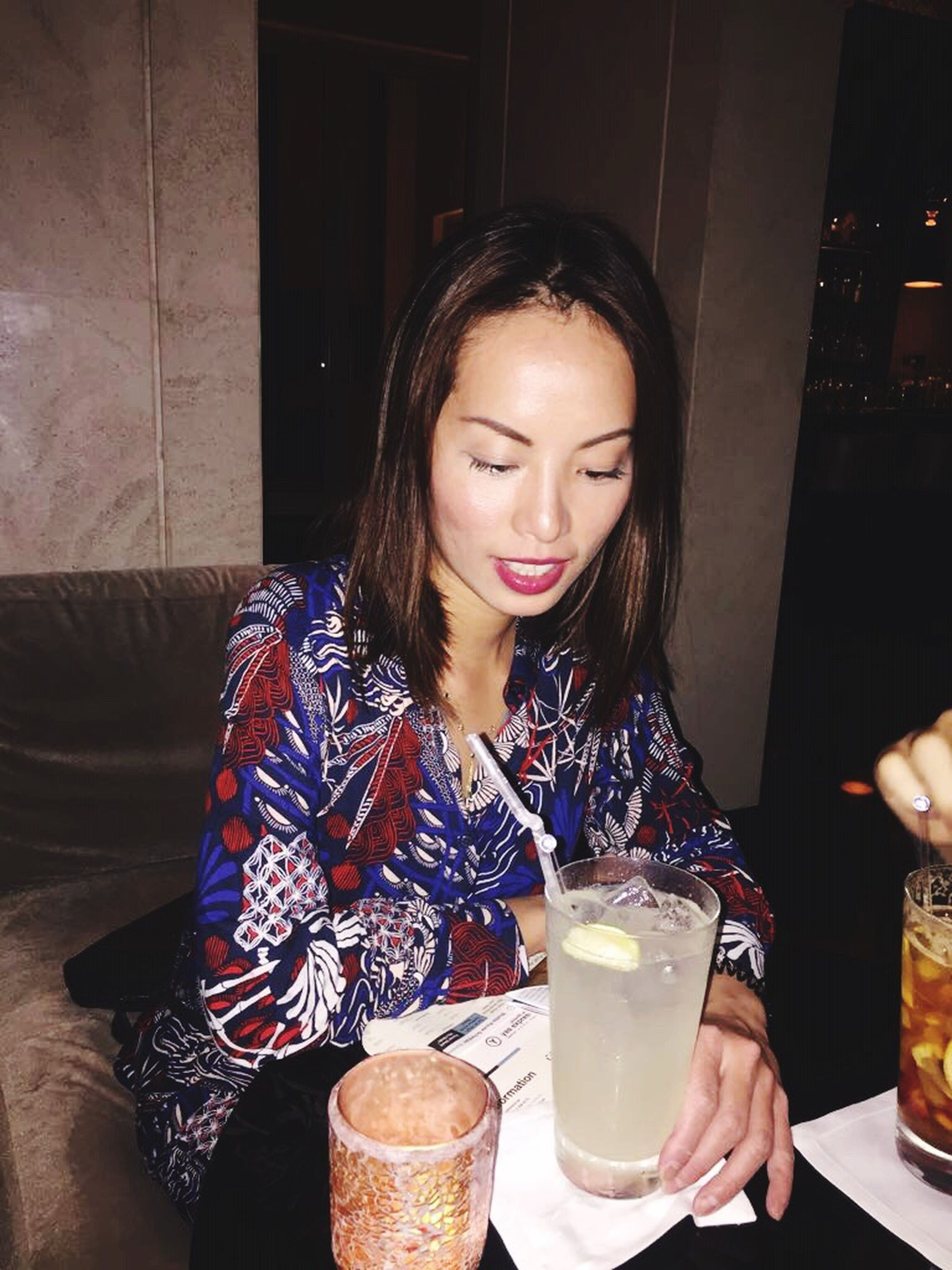 drink, food and drink, table, refreshment, freshness, sitting, leisure activity, lifestyles, indoors, young women, drinking, coffee cup, coffee - drink, spoon, young adult, restaurant, casual clothing, holding, person, hot drink