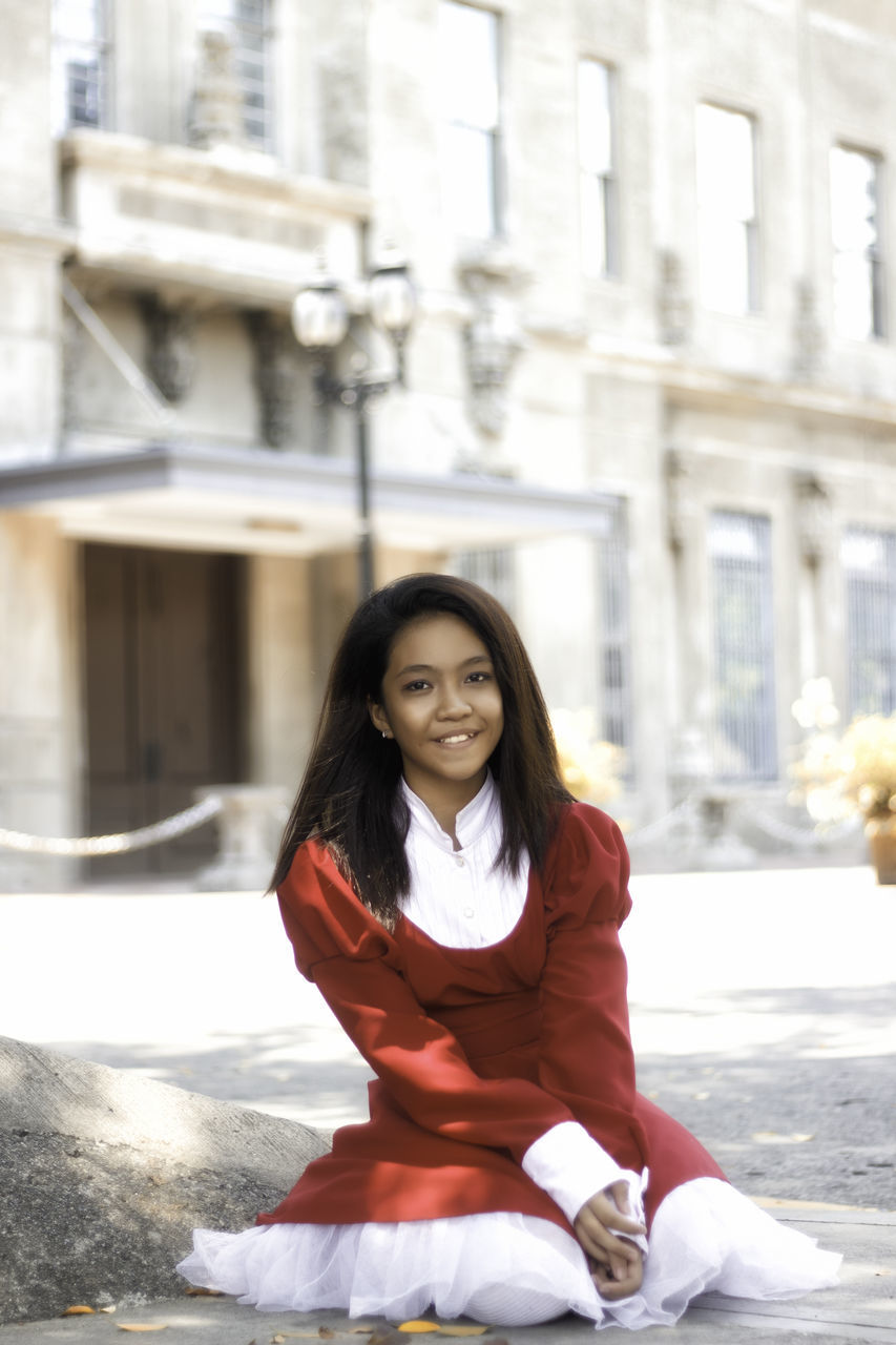 one person, real people, building exterior, architecture, looking at camera, built structure, portrait, smiling, outdoors, lifestyles, happiness, front view, leisure activity, young women, day, young adult, city, standing, beautiful woman, people