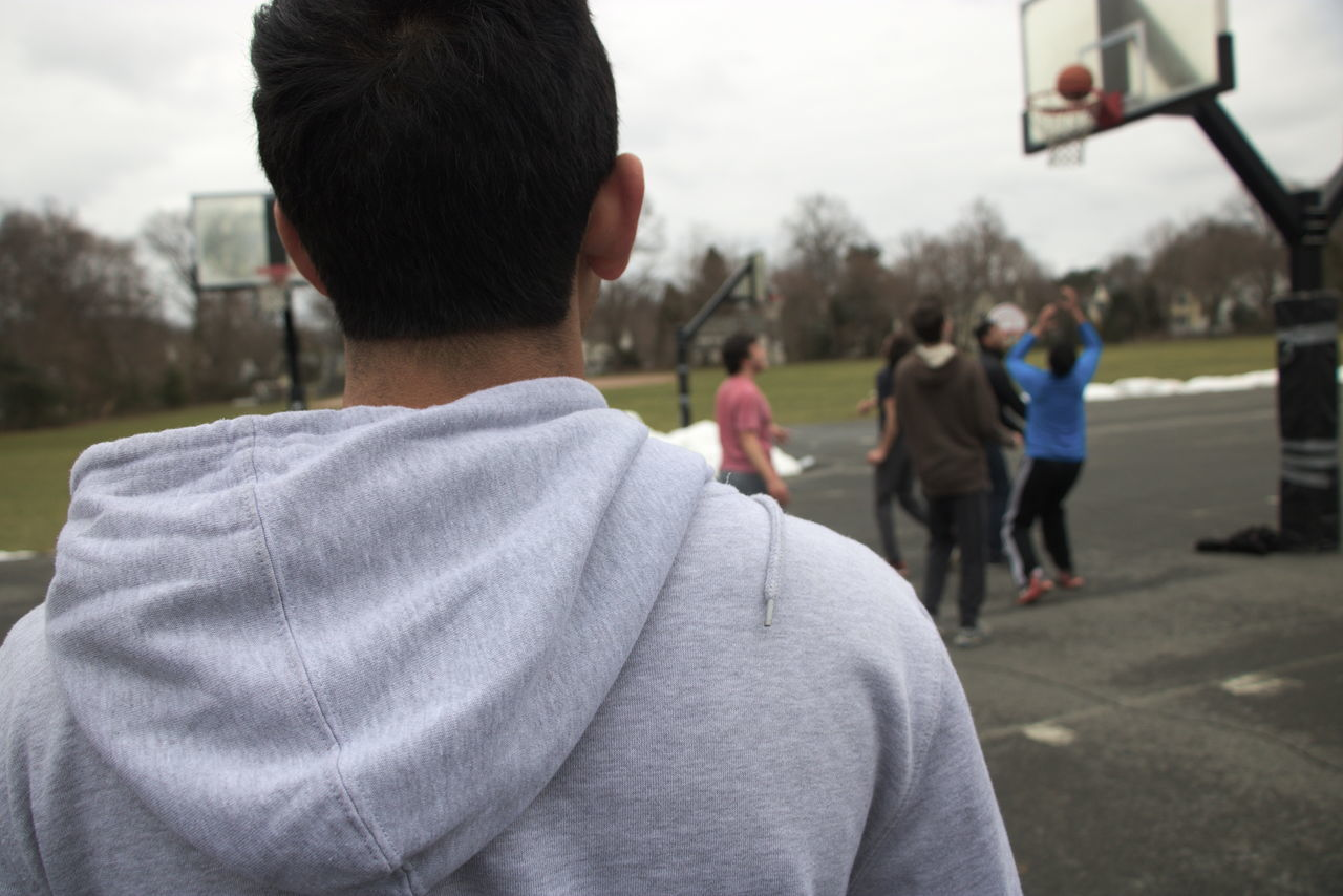 Pickup basketball player watches from the sidelines. Alone Basketball Basketball Game Bullying Day Exclusion Focus On Foreground Friends Men Outdoors Over The Shoulder View Overcast People Pickup Ball Real People Rear View Sideline Solitary Solitude Watching Breathing Space