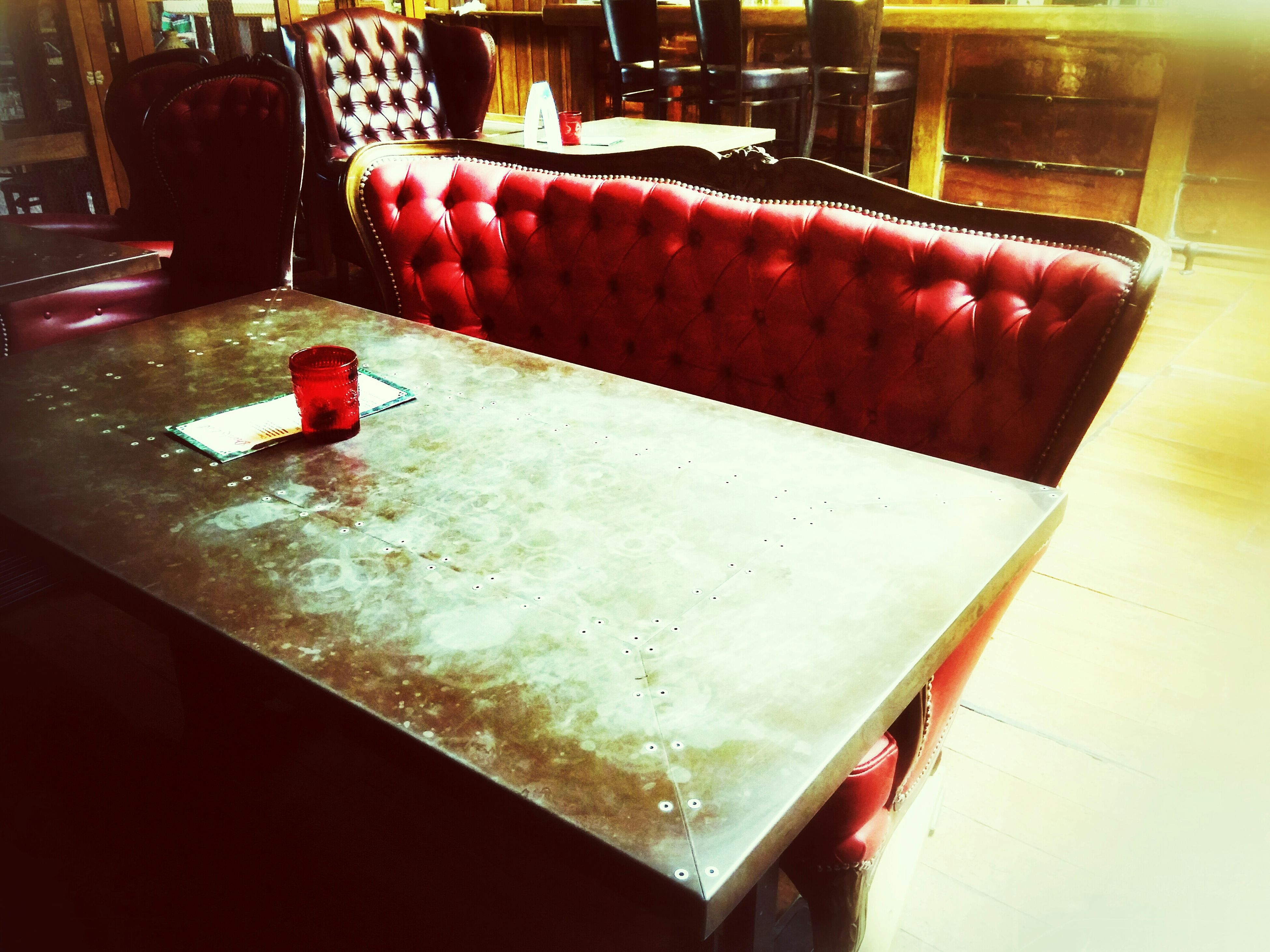 indoors, table, red, still life, food and drink, restaurant, glass - material, empty, close-up, absence, no people, drinking glass, illuminated, chair, focus on foreground, freshness, home interior, high angle view, wood - material, transparent