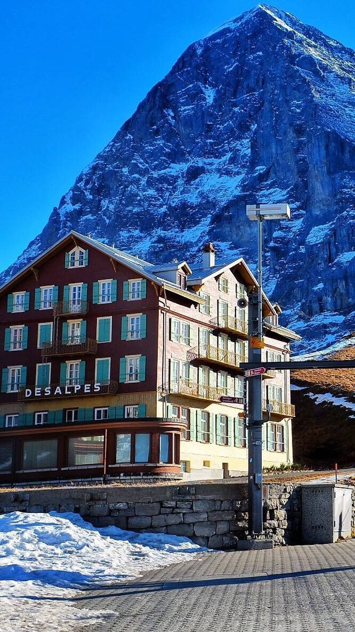 snow, building exterior, winter, cold temperature, architecture, built structure, house, mountain, window, snowcapped mountain, residential building, outdoors, no people, day, frozen, mountain range, nature, travel destinations, blue, landscape, scenics, clear sky, sky, city, snowdrift, beauty in nature