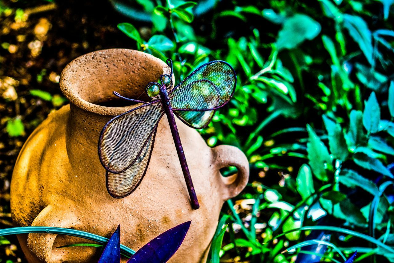 Close-Up Of Artificial Dragonfly Perching On Pot