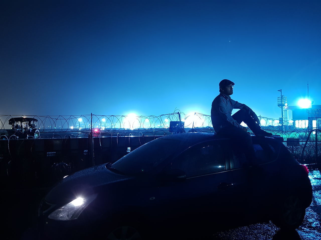 night, illuminated, car, transportation, blue, one person, clear sky, real people, mode of transport, standing, outdoors, men, full length, young adult, sky, architecture, people