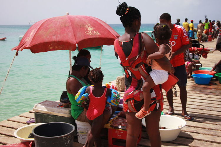 Beach Umbrella Capo Verde Clients Day Mother And Child Outdoors People Sal Island Santa Maria Sea Selling Fish Summer 2015 Togetherness Water Wooden Pier