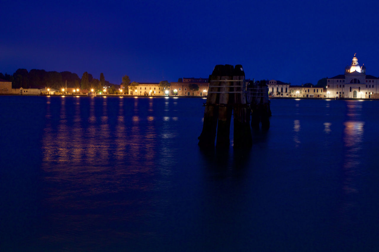 Wooden Posts On River By Illuminated Buildings Against Clear Sky At Night